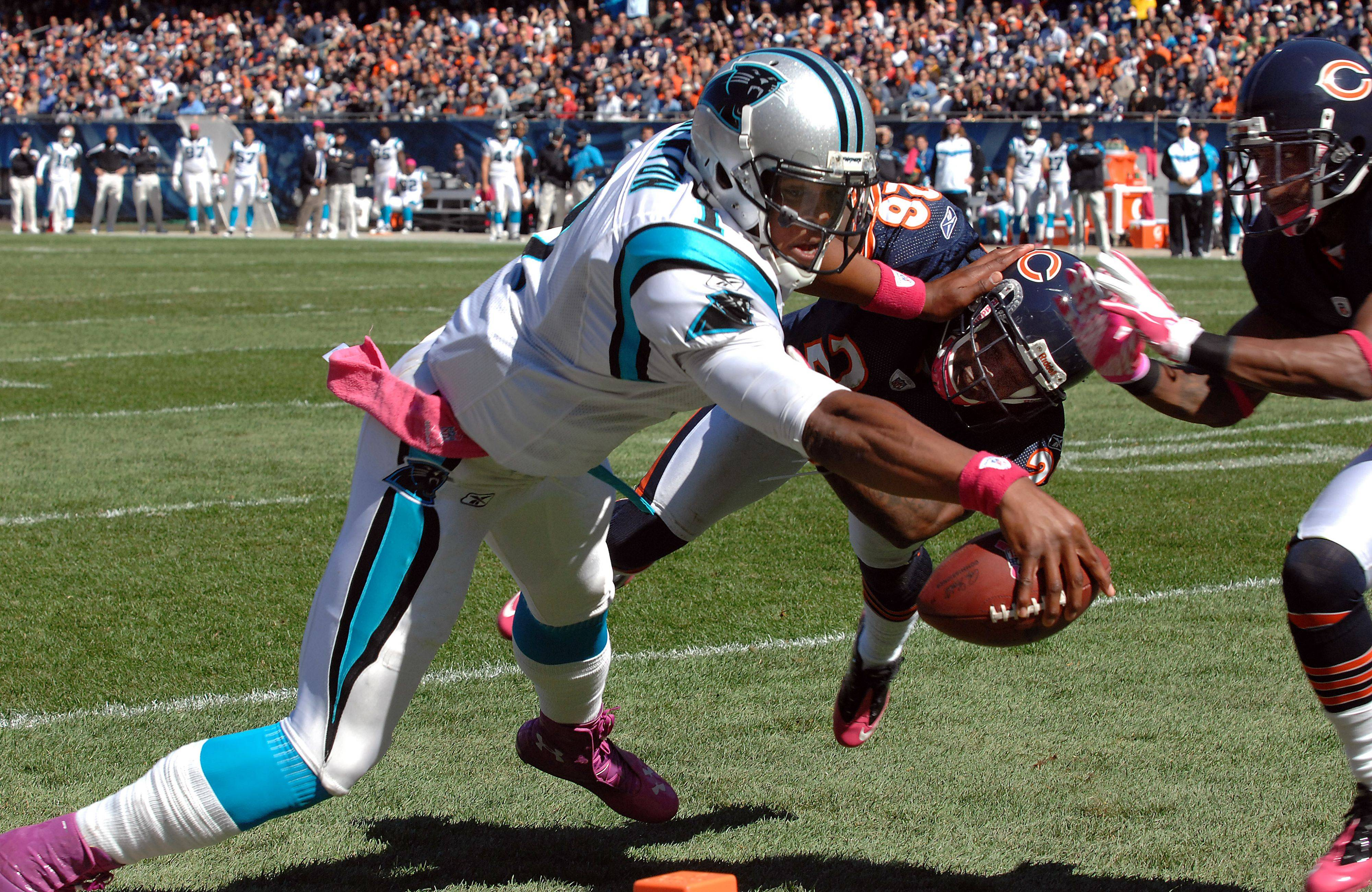 Panthers quarterback Cam Newton pushes away the Bears' defense Sunday as he scores a first-quarter touchdown.