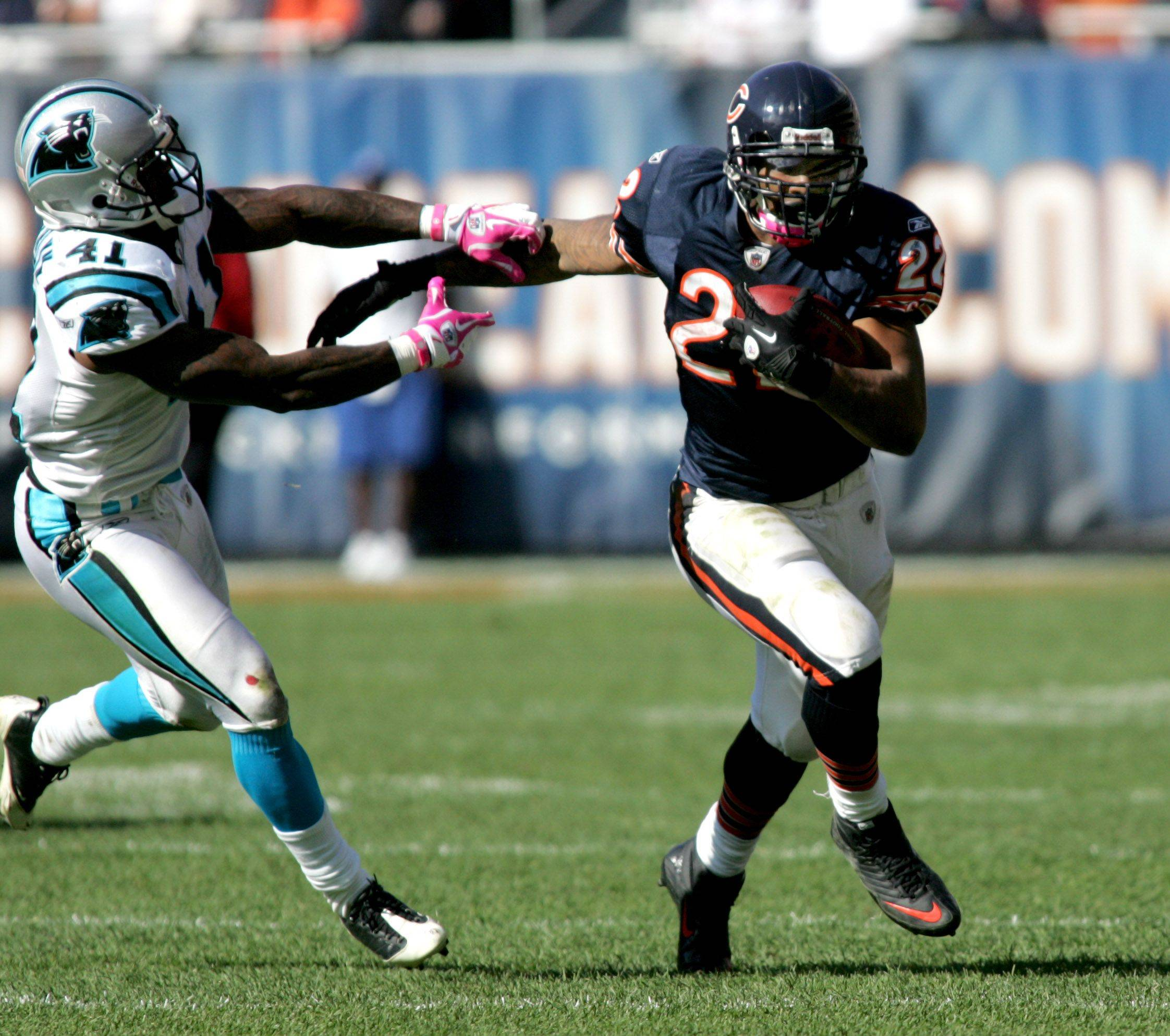 Matt Forte of the Chicago Bears with the ball as Captain Munnerlyn of Carolina Panthers moves in for a tackle.
