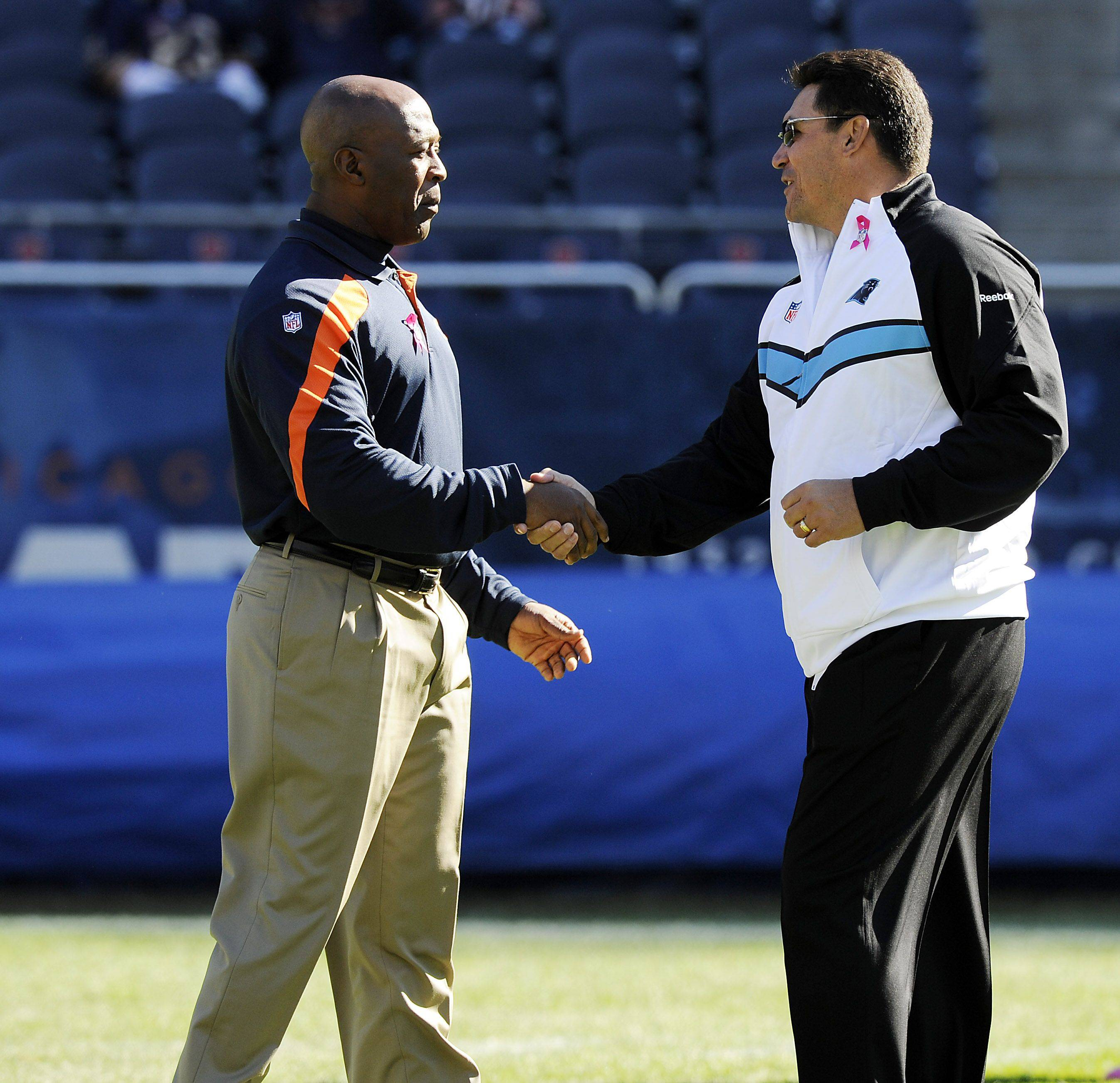 Chicago Bears coach Lovie Smith greets Panthers head coach Ron Rivera before the game as they get ready to play.