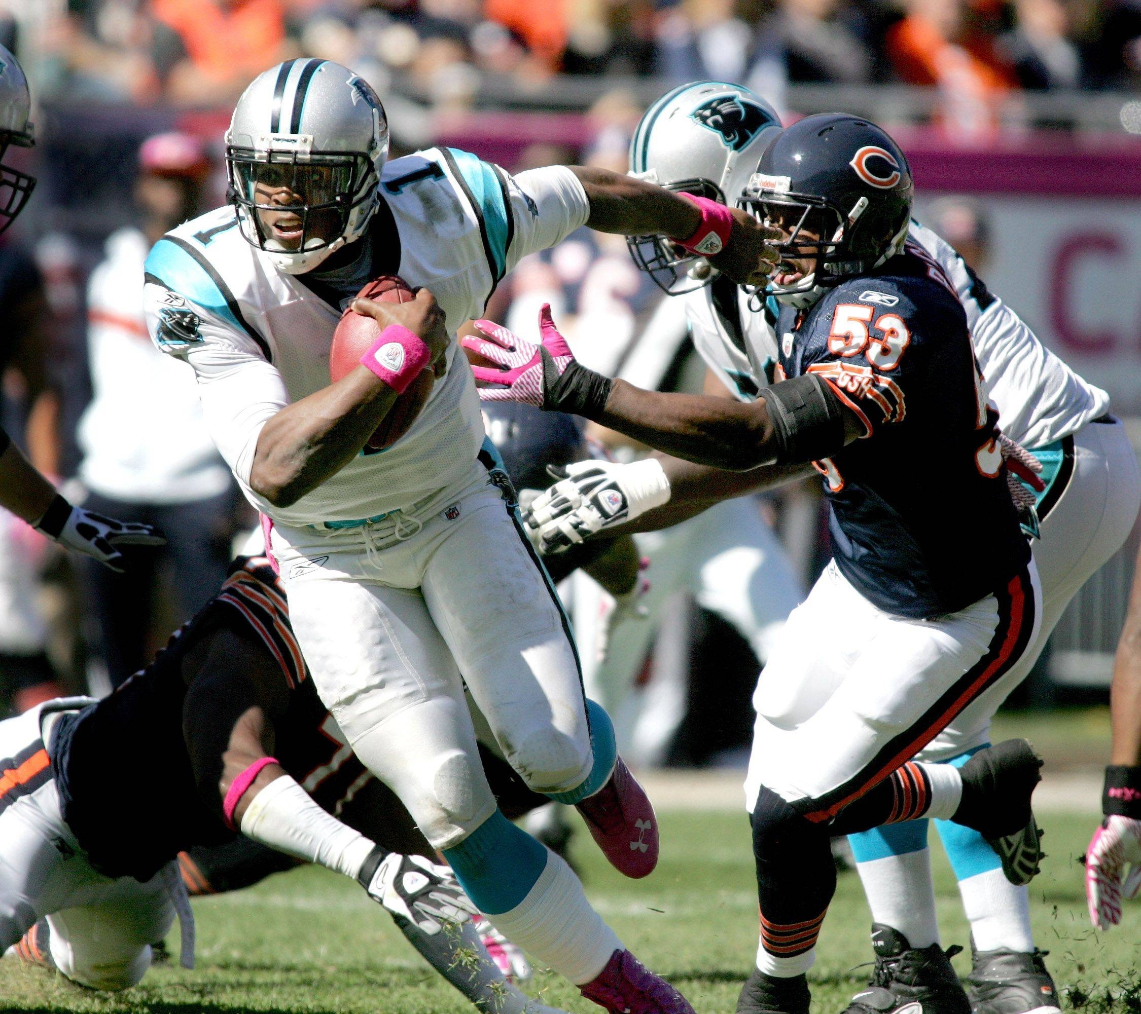 Carolina Panthers quarterback Cam Newton fends off Nick Roach, right, of the Chicago Bears at Soldier Field.
