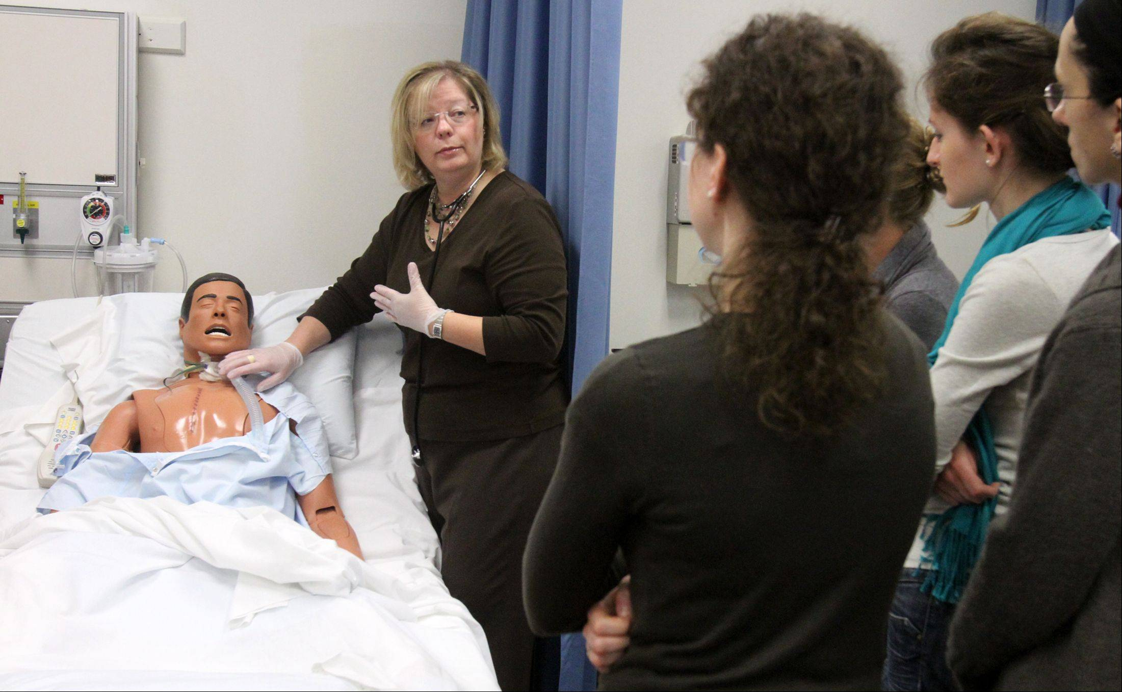Dawn Kuerschner, associate professor, instructs nursing program students using a human patient simulator at Oakton Community College in Des Plaines. The simulator was purchased by the college's foundation.