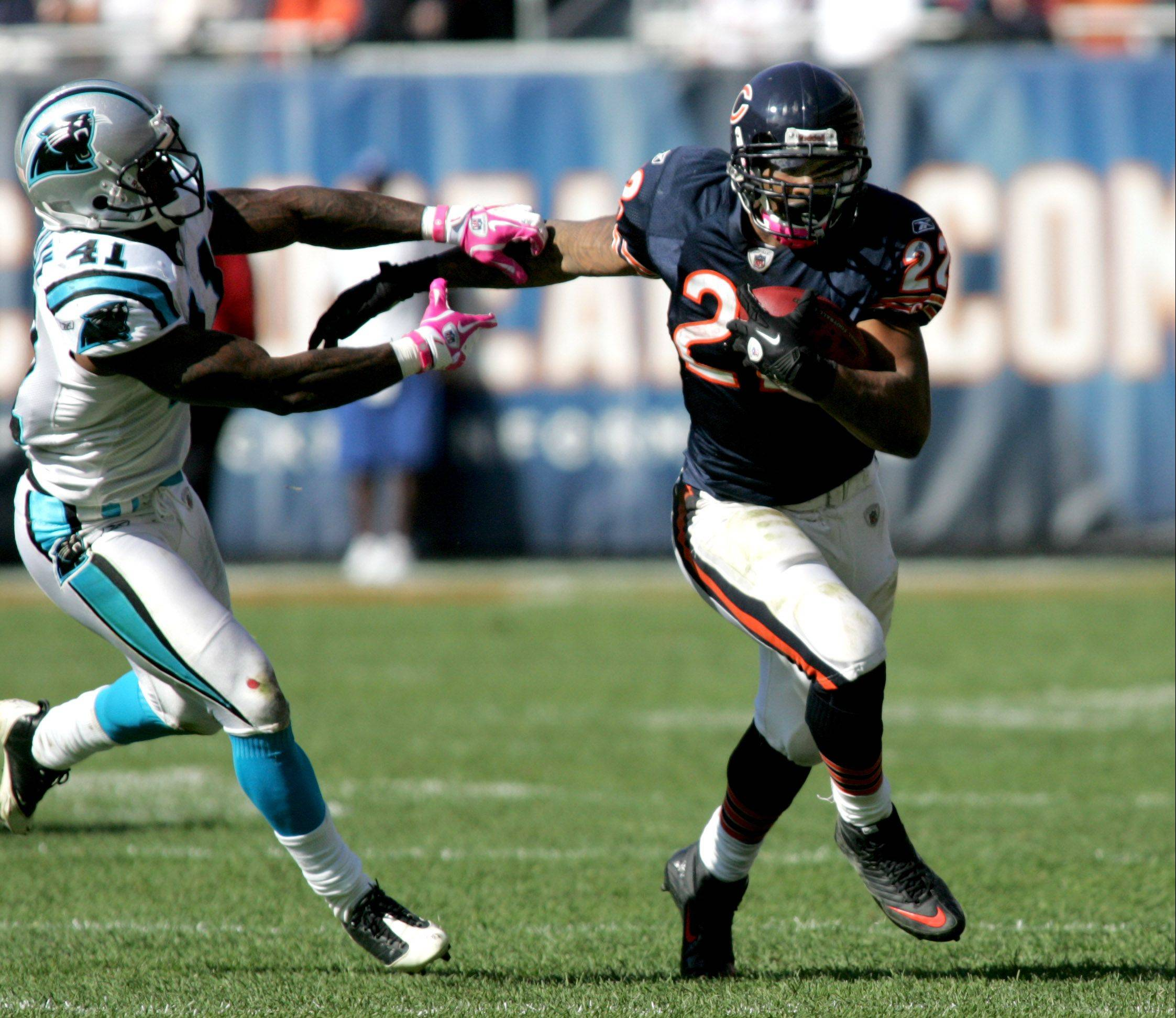 Matt Forte of the Bears with the ball as Captain Munnerlyn of Carolina Panthers oves in for a tackle at Soldier Field on Sunday.
