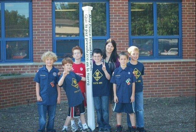 Cub Scouts from Pack 468 and Ivy Hill Principal Kristy Csensich stand around the newly planted peace pole outside the school's entrance.