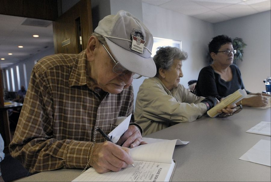 Herman Langhans signs in as he and Connie Green and Nancy Wooley wait to talk to an assessor about their property tax bills at the Elk Grove Township office. Suburban assessors' offices were flooded with visitors and phone calls Tuesday after property tax bills began showing up in residents' mailboxes.