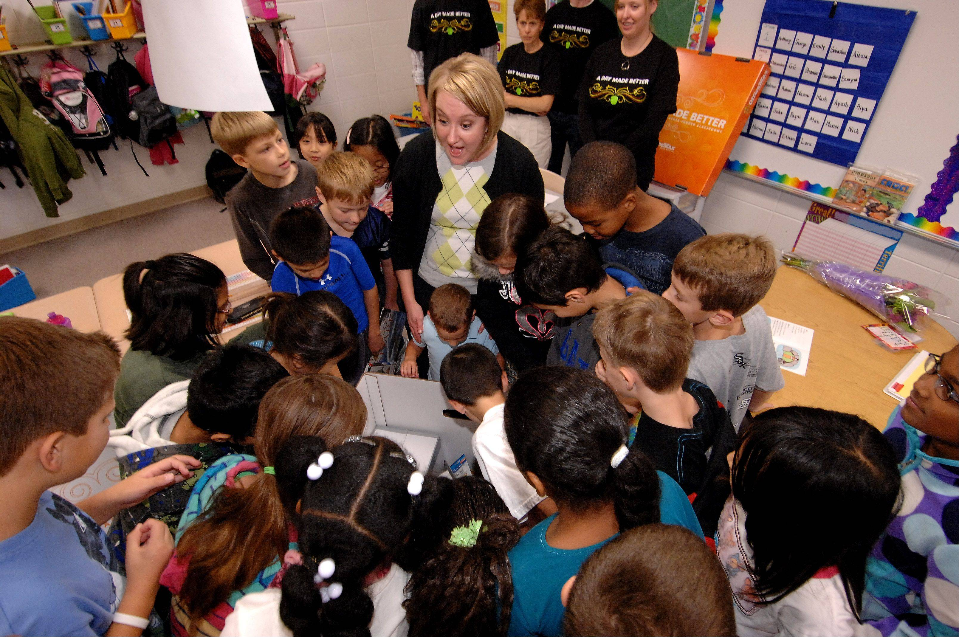 Third-grade teacher Becky Sikora opens a box full of supplies with her students Tuesday at Welch Elementary School in Naperville. Sikora was one of three Indian Prairie Unit District 204 teachers to receive $1,000 worth of supplies from OfficeMax as part of the company's national A Day Made Better campaign.