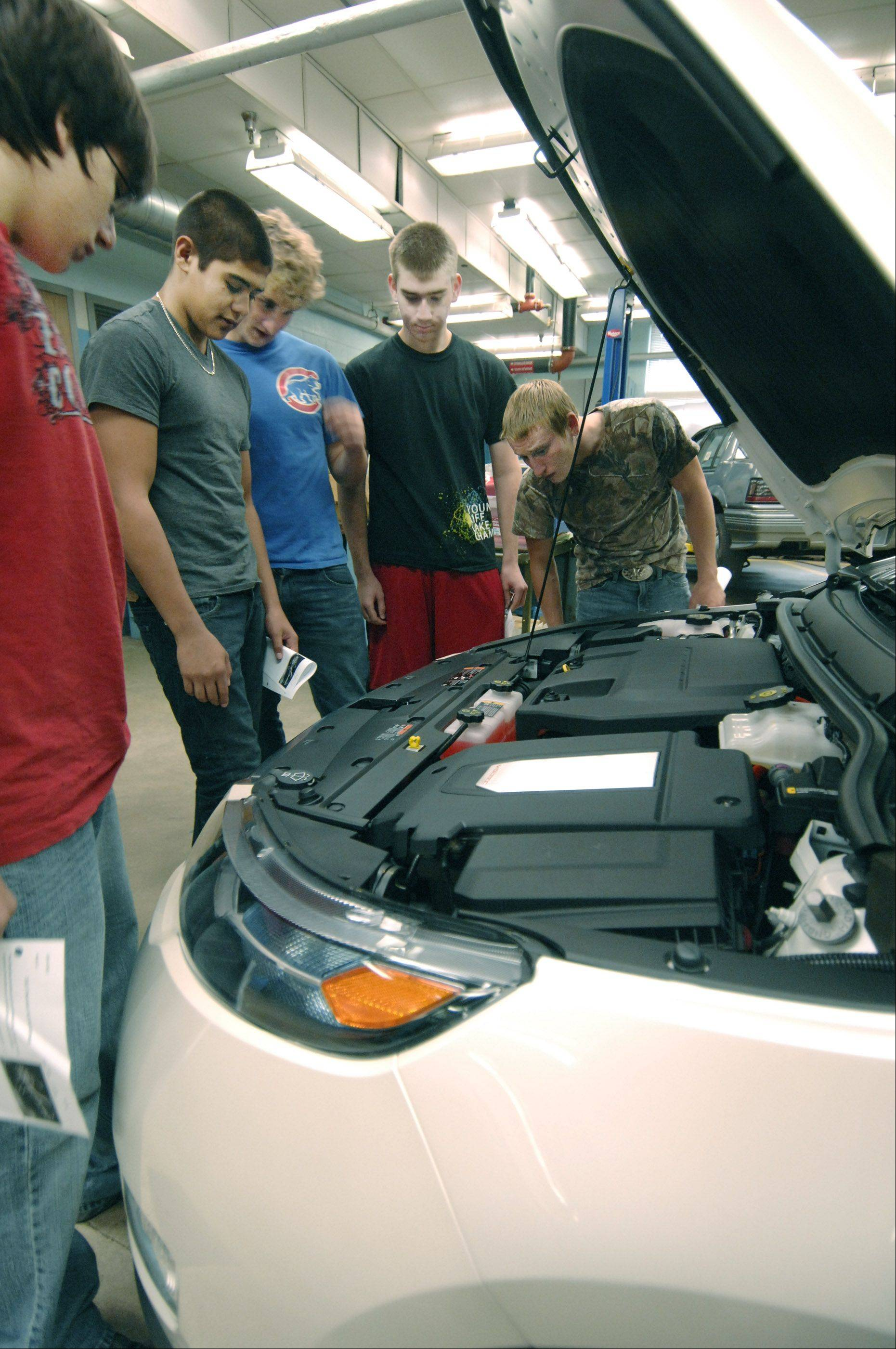 Students in an automotive technology class at Willowbrook High School in Villa Park examine the engine and motor compartment in a Chevy Volt electric car.