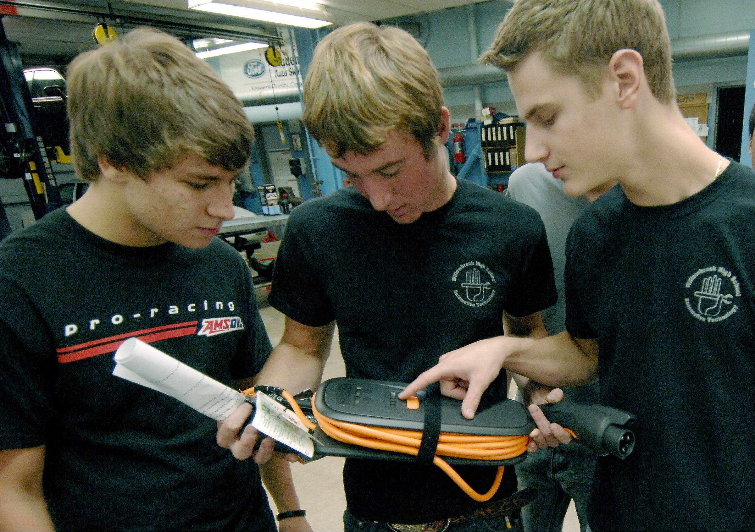 Nicholas Sedlacek, Ben Rispens and Ryan Orlando look at the charging cable of a Chevy Volt during the electric car's stop in their automotive technology class at Willowbrook High School in Villa Park.