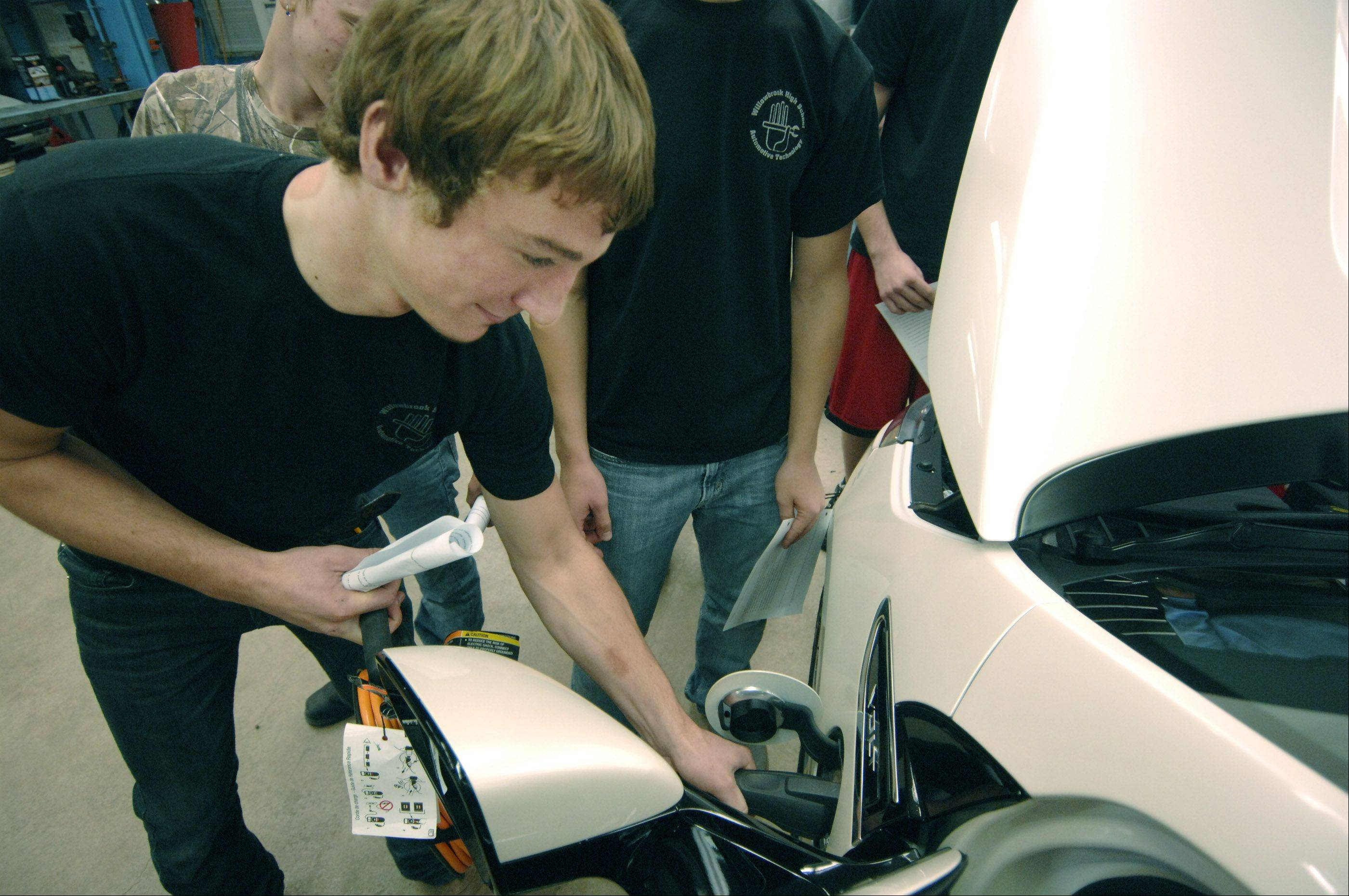 Ben Rispens plugs the charging cord into a Chevy Volt on display Sept. 28 at Willowbrook High School in Villa Park.