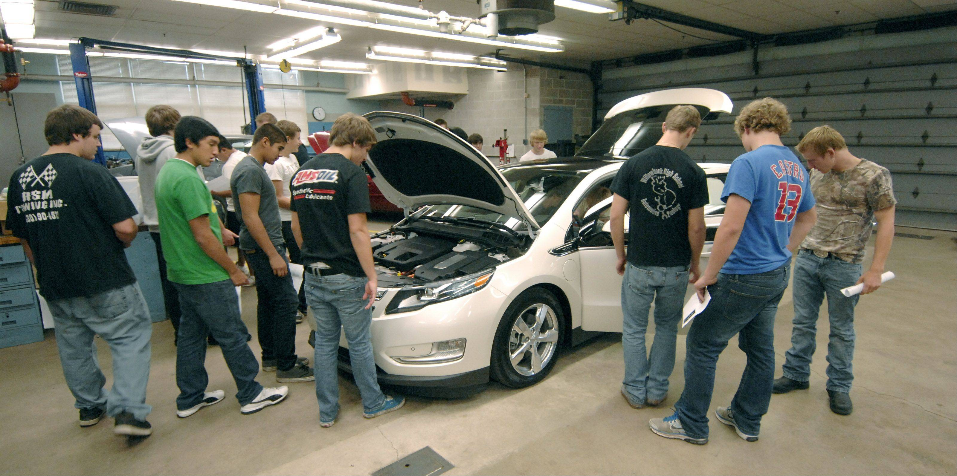 Students in an automotive technology class at Willowbrook High School in Villa Park take a close look at a Chevy Volt electric car.