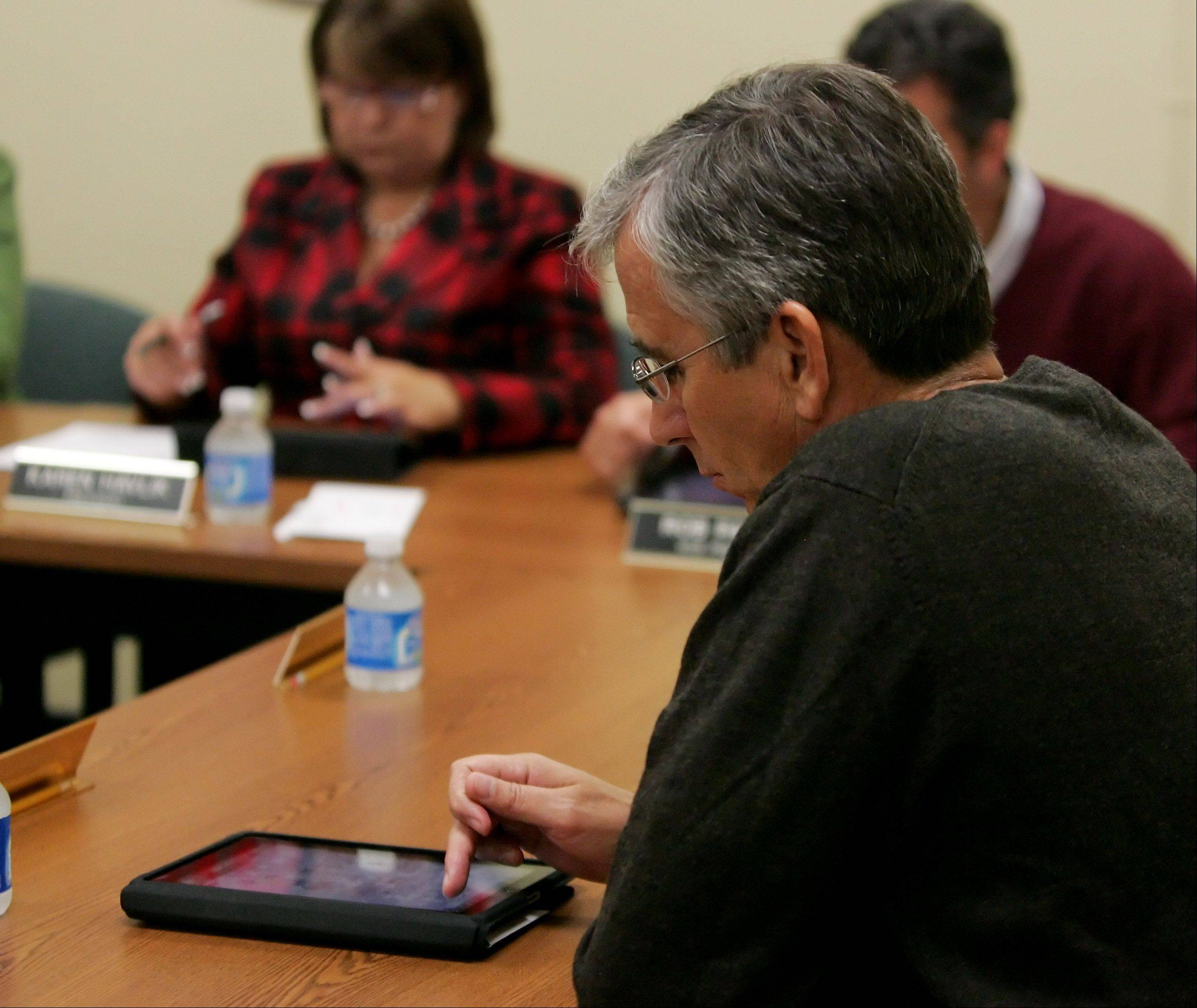 Mundelein High School board member Edwin Specht works on his Apple iPad during a recent meeting. The board is among the few in the suburbs that has gone paperless with iPads.