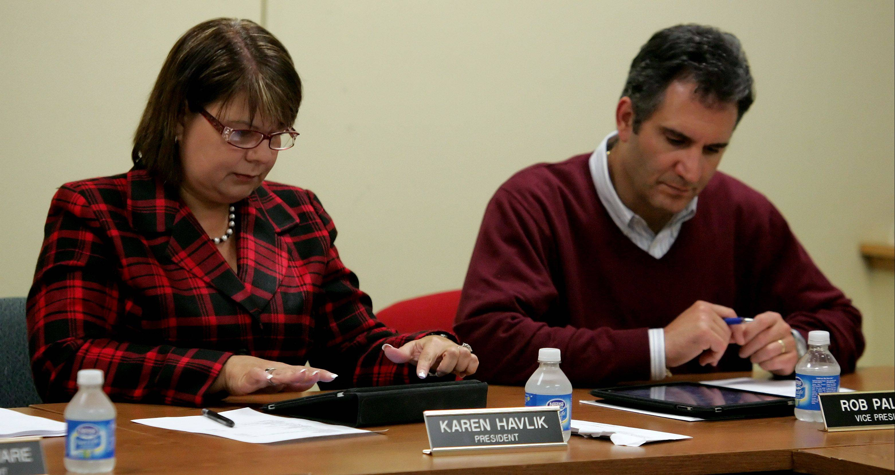 School board members Karen Havlik and Rob Paliani work on their Apple iPads during the Mundelein High School board meeting Tuesday. Sept. 27. The iPads cost about $500 to $800 each, but are expected to save money in paper costs and are more environmentally friendly.