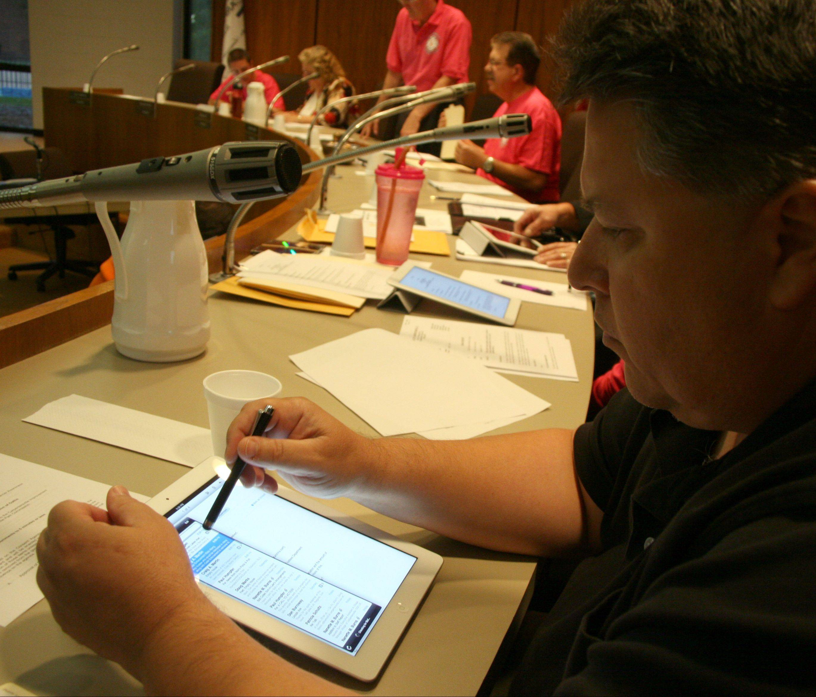 Village Trustee Doug Marks reads documents on his village-issued iPad before a village of Carpentersville Board Meeting on Tuesday night at village hall.