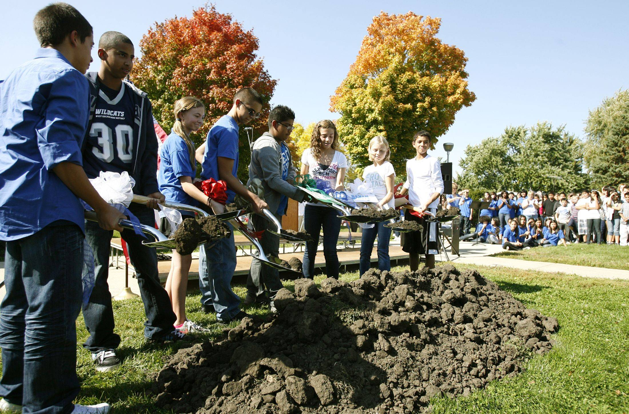 Students participate in a groundbreaking celebration for the West Chicago Middle School expansion. Jonathon Valdivia, Mikey Bibbs, Kendra Whelan, Tony Martin, Eric Santana, Lauren Long, Jenna Palka and Tai Bibbs gather dirt on their ceremonial shovels.