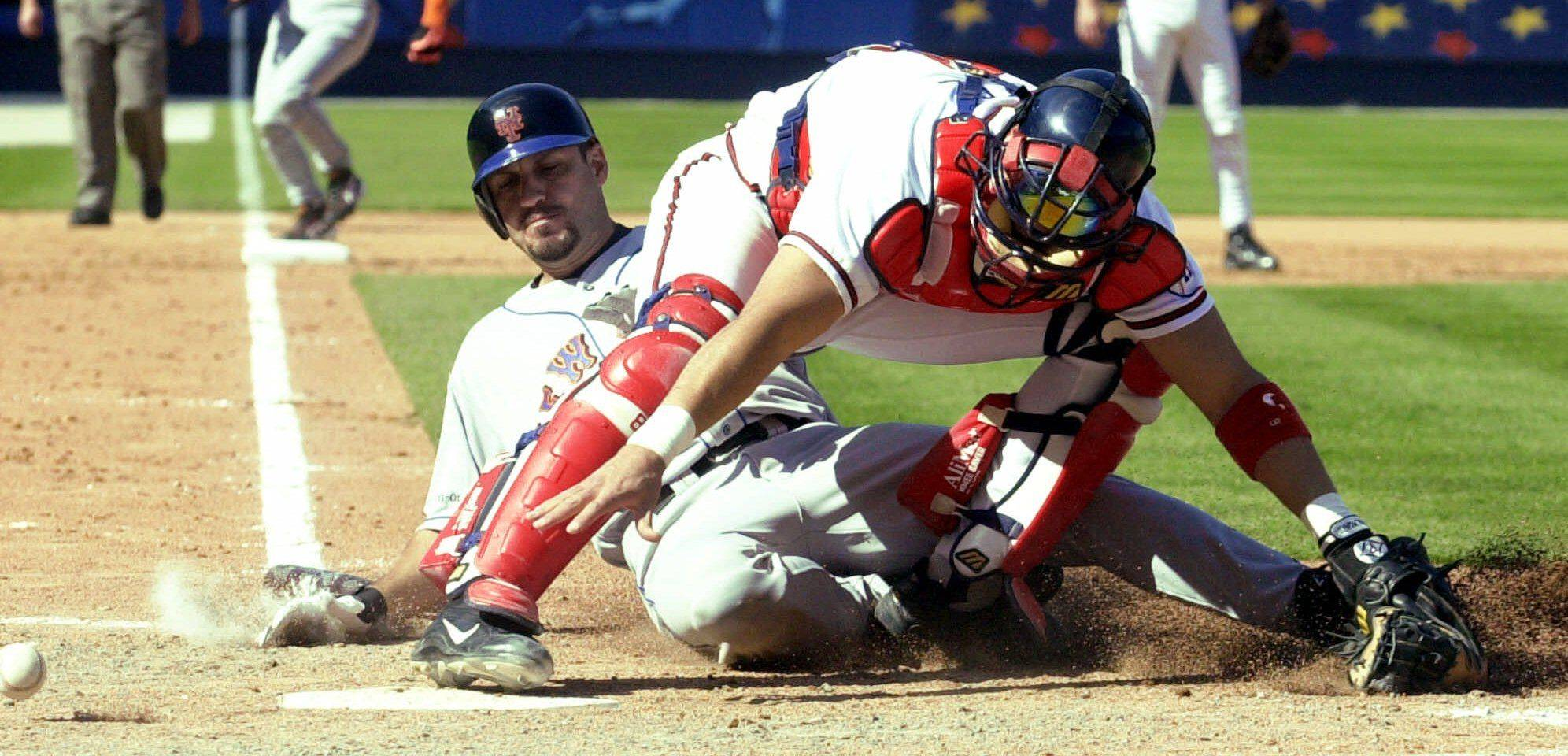 New York Mets Robin Ventura scores in the eighth inning as the ball gets away from Atlanta Braves catcher Javy Lopez at Turner Field in Atlanta Sunday, Sept. 30, 2001. Lopez injured his ankle on the play and left the game.