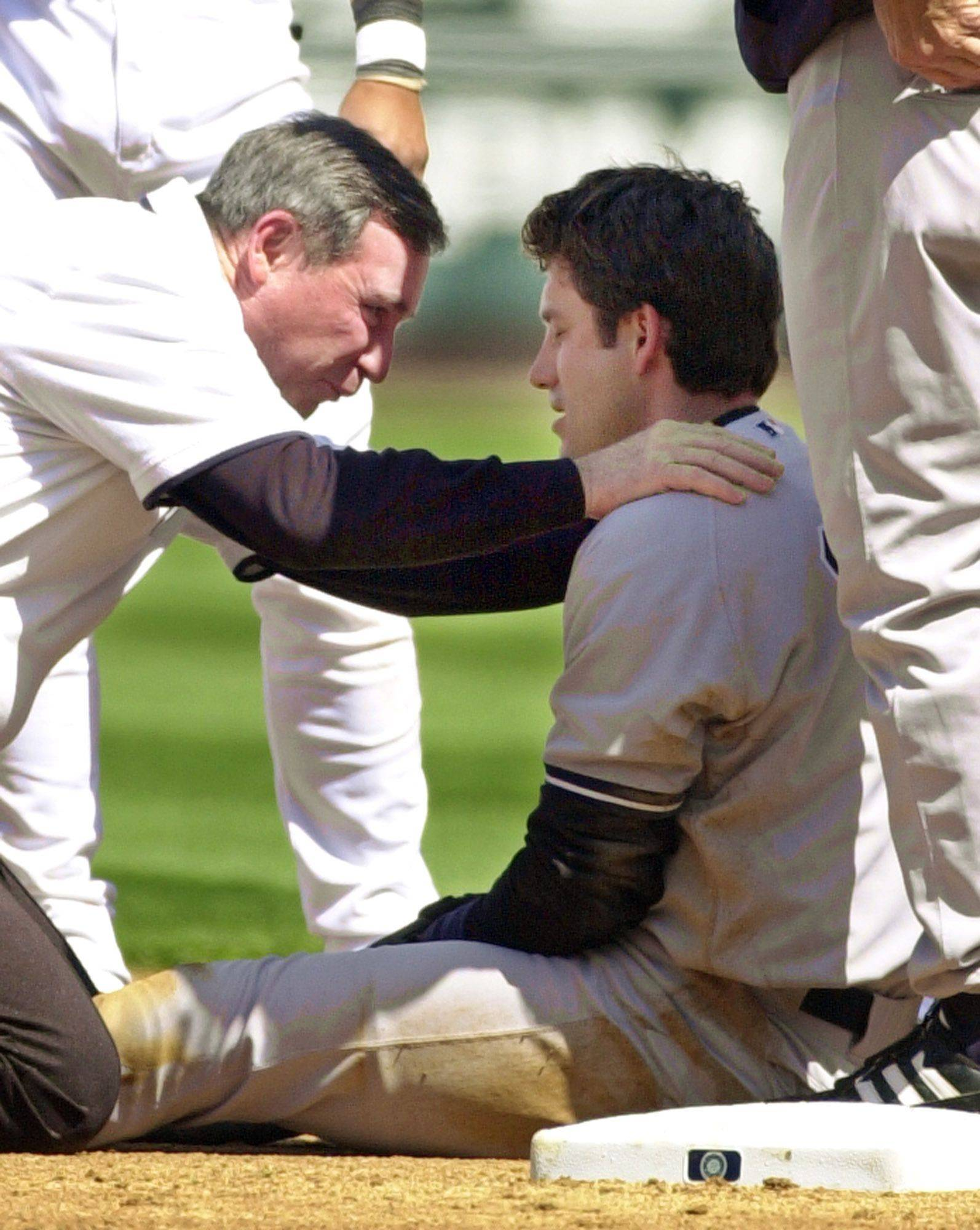 New York Yankees' Robin Ventura, right, is checked by trainer Gene Monahan following a second inning collision with Seattle Mariners shortstop Carlos Guillen Sunday, April 28, 2002, in Seattle. Ventura left the game.