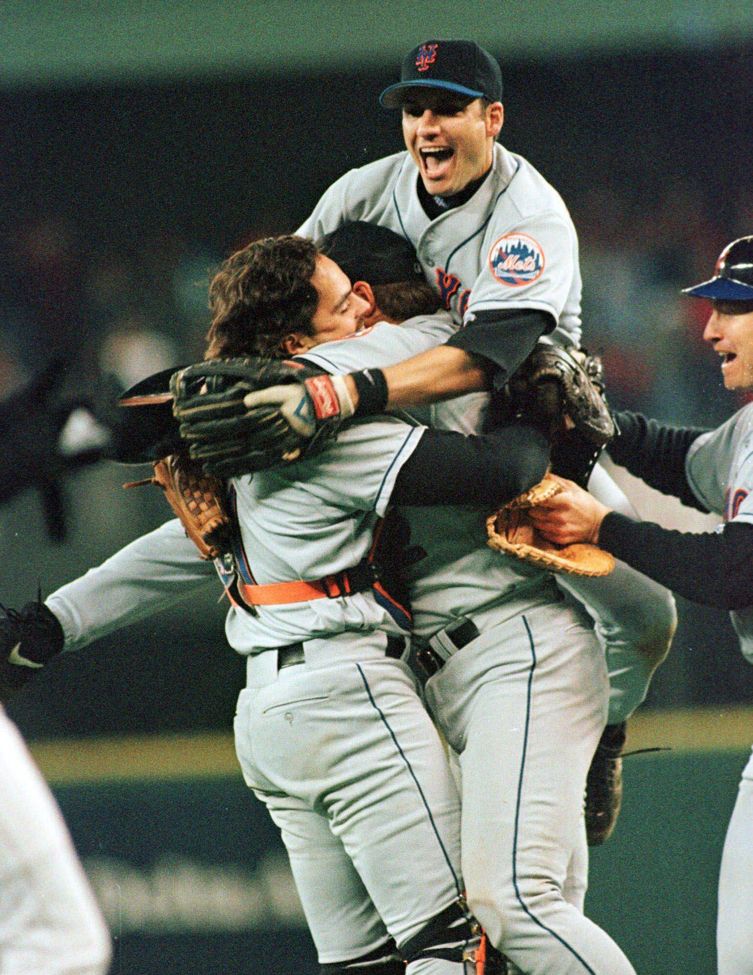 New York Mets Robin Ventura jumps on top of catcher Mike Piazza and pitcher Al Leiter after the Mets defeated the Cincinnati Reds 5-0, Monday, Oct. 4,1999, in Cincinnati. John Olerud is at right.