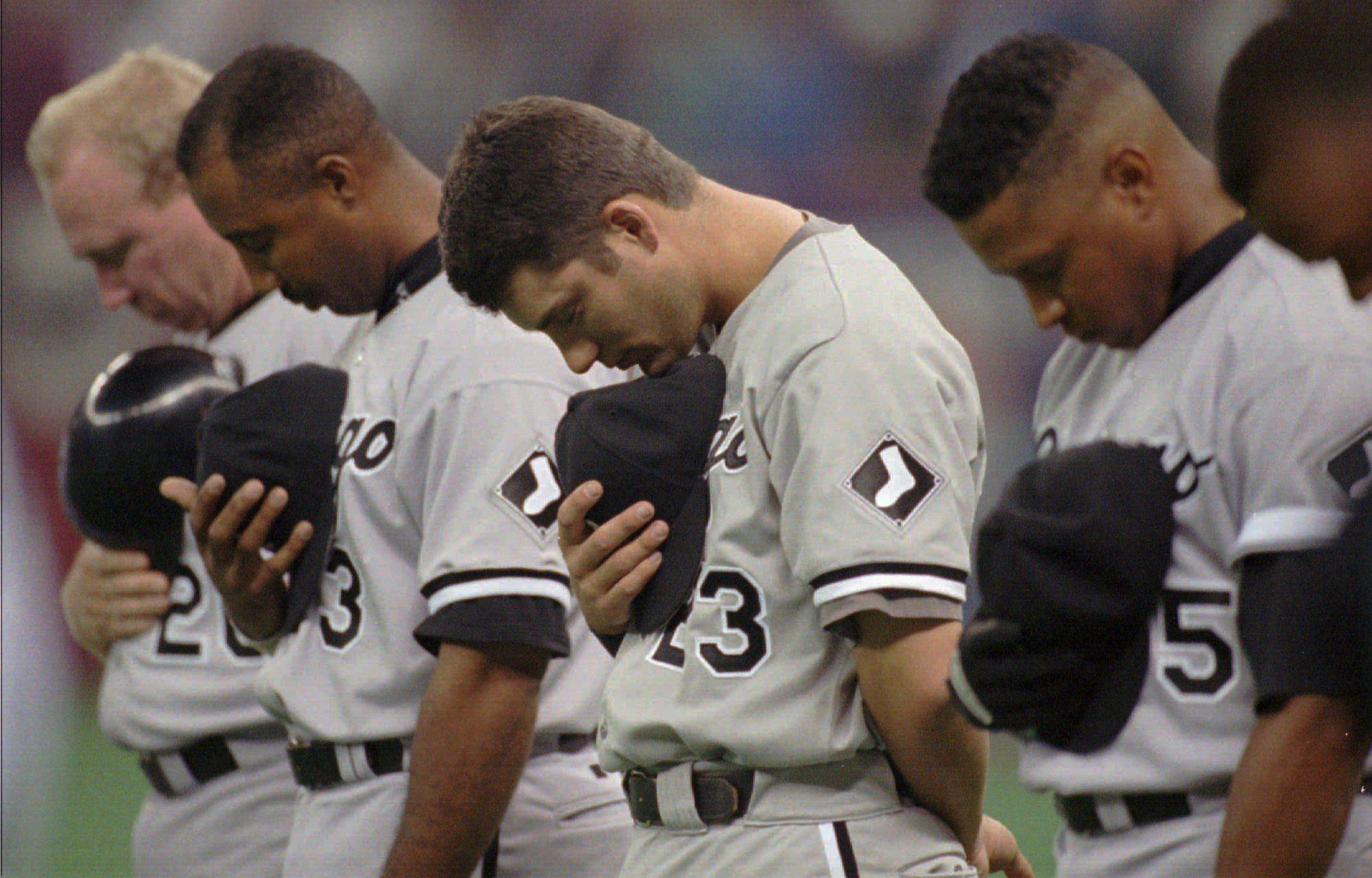 Chicago White Sox Ron Karkovice, left, Harold Baines, Robin Ventura and Danny Tartabull bow their heads during a moment of silence before their game against the Seattle Mariners Tuesday, April 2, 1996, in Seattle, in honor of umpire John McSherry. McSherry collasped and died during a ball game Monday. The Mariners won, 3-2.