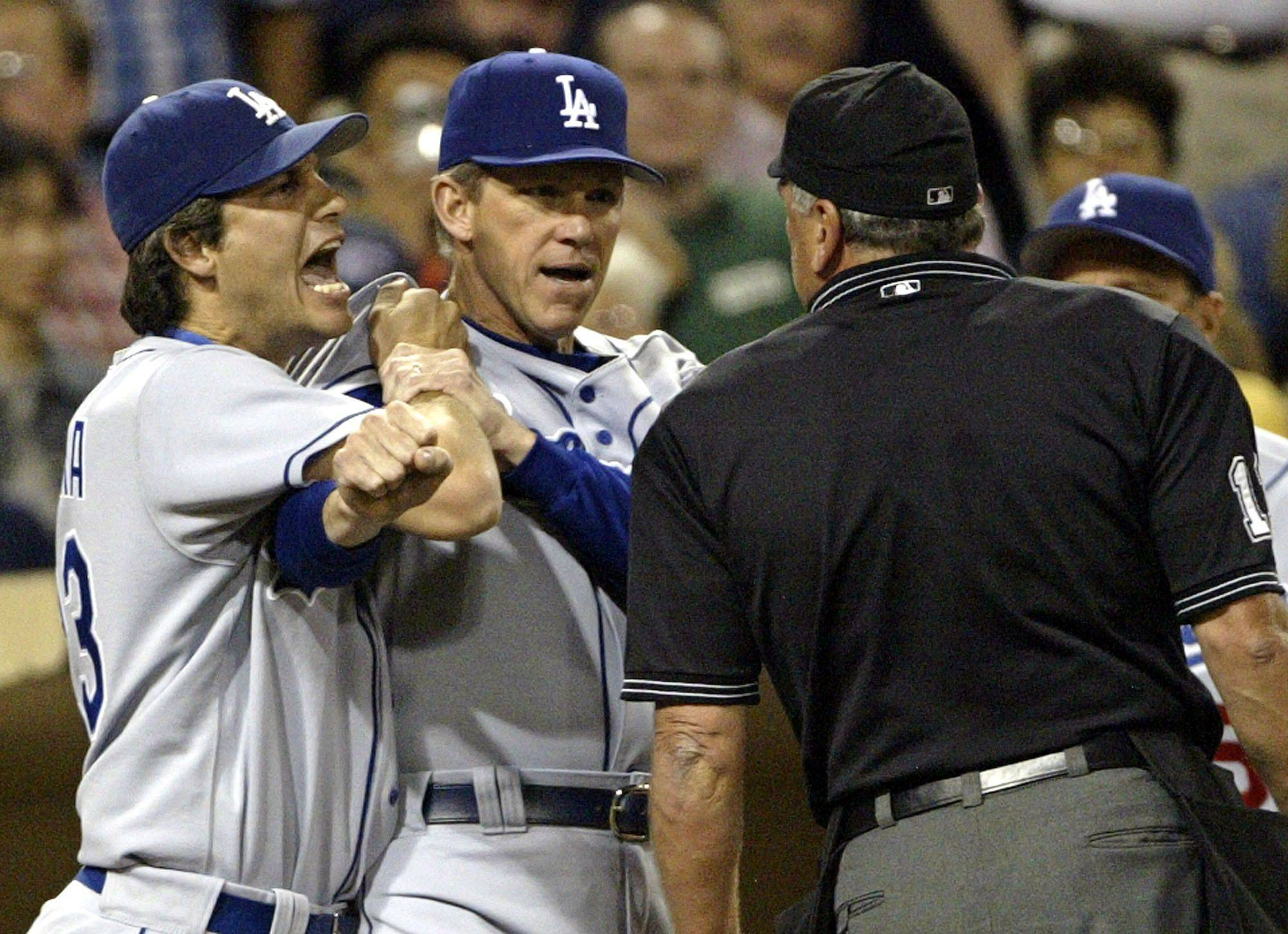 Los Angeles Dodgers manager Jim Tracy, center, holds back Robin Ventura, left, as Ventura screams at umpire Ed Montague in the seventh inning of the Dodgers' game with the San Diego Padres on Thursday, Sept. 23, 2004, in San Diego. Montague had called out Ventura on strikes in the previous inning.