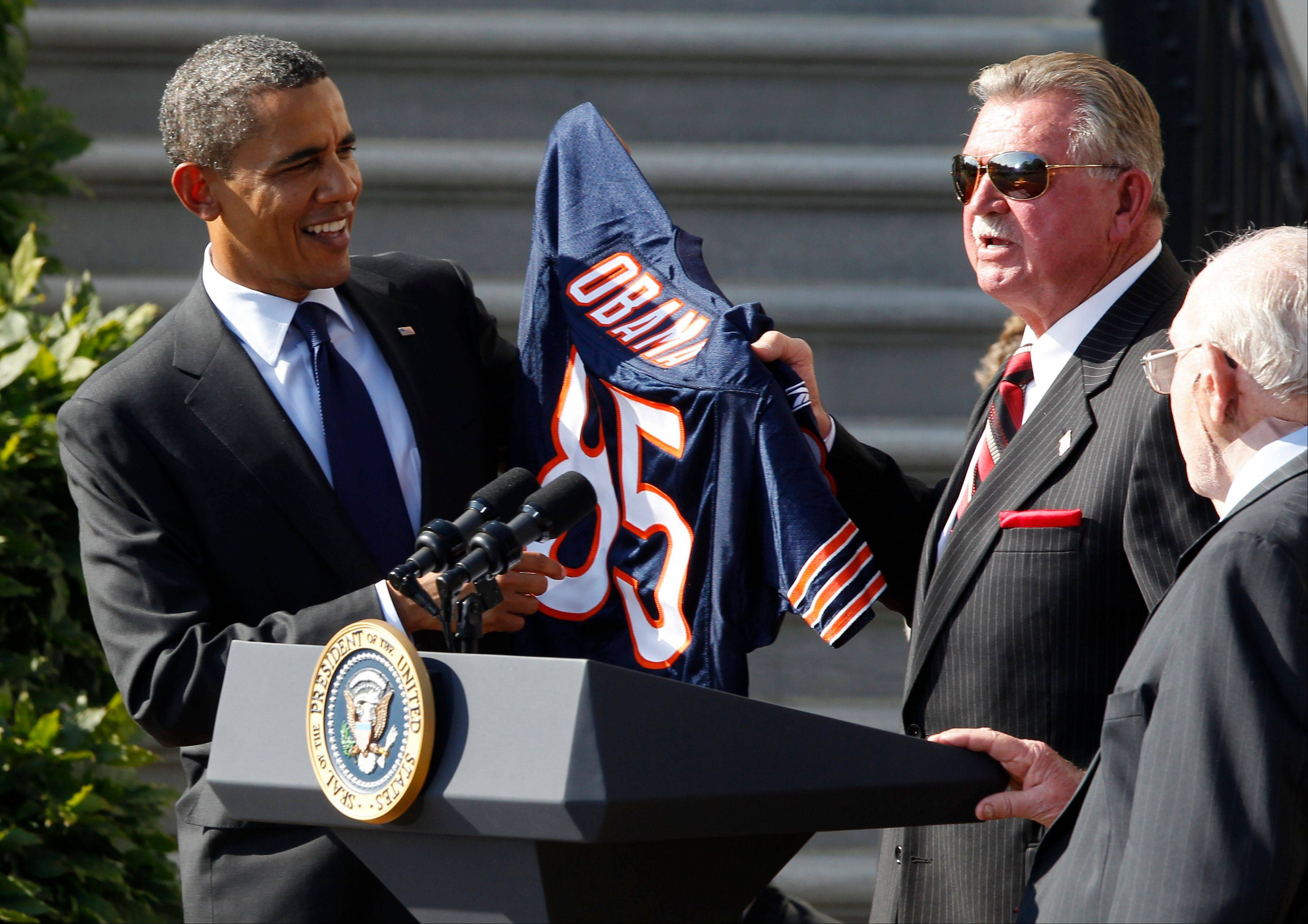 President Barack Obama is presented with a team jersey by head coach Mike Ditka as defensive coordinator Buddy Ryan stands at right as the 1985 Super Bowl XX Champions Chicago Bears football team are honored at a ceremony on the South Lawn of the White House in Washington, Friday, Oct. 7, 2011.