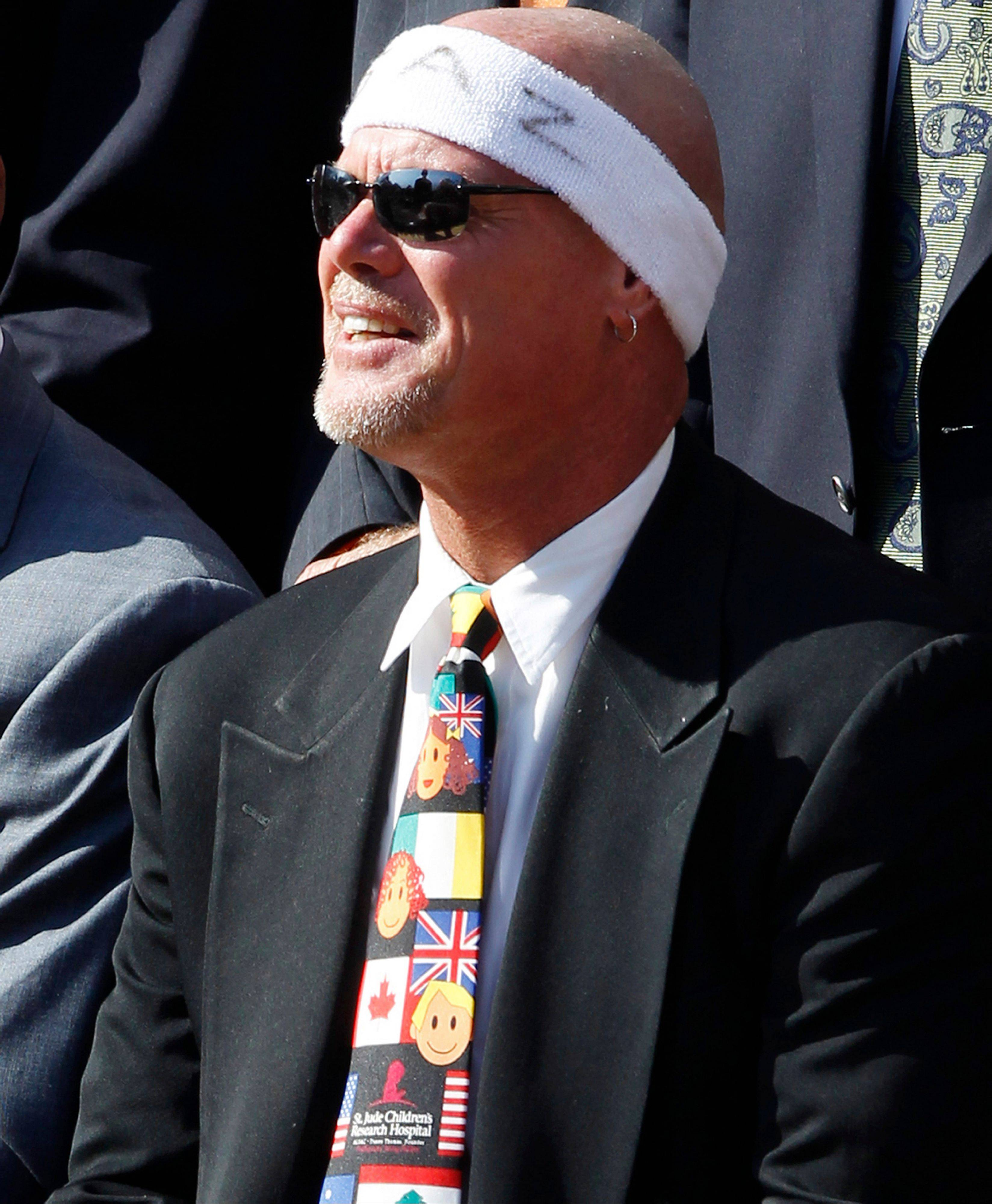 Former quarterback Jim McMahon listens as President Barack Obama honors the 1985 Super Bowl XX Champions Chicago Bears football team during a ceremony on the South Lawn of the White House in Washington, Friday, Oct. 7, 2011.