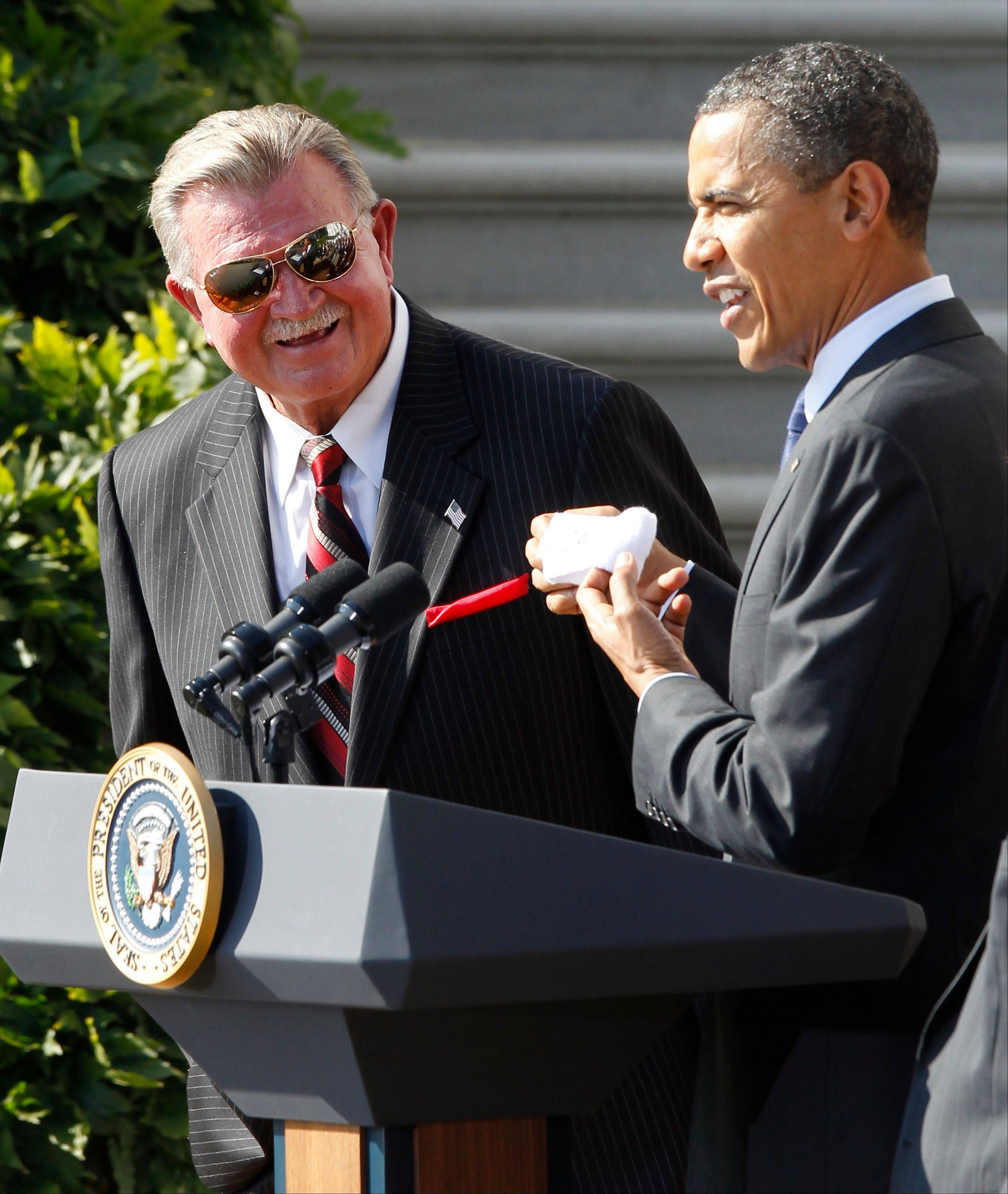 President Barack Obama holds up a headband given to him by quarterback Jim McMahon as he stands with head coach Mike Ditka as he honors the 1985 Super Bowl XX Champions Chicago Bears football team during a ceremony on the South Lawn of the White House in Washington, Friday, Oct. 7, 2011.