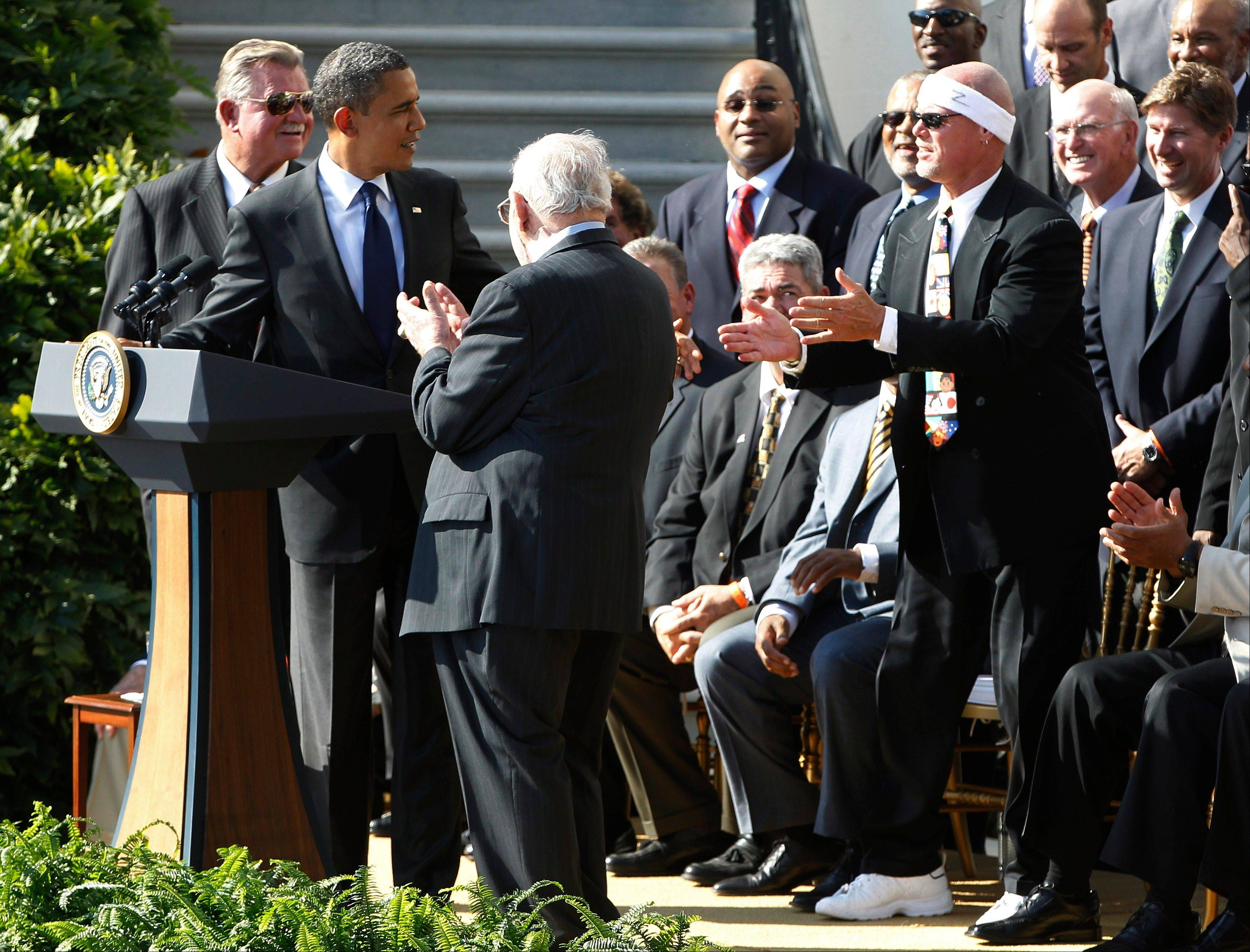 President Barack Obama looks towards quarterback Jim McMahon, wearing headband, right, as he stands with head coach Mike Ditka, left, and defensive coordinator Buddy Ryan, third left, as he honors the 1985 Super Bowl XX Champions Chicago Bears football team during a ceremony on the South Lawn of the White House in Washington, Friday, Oct. 7, 2011.