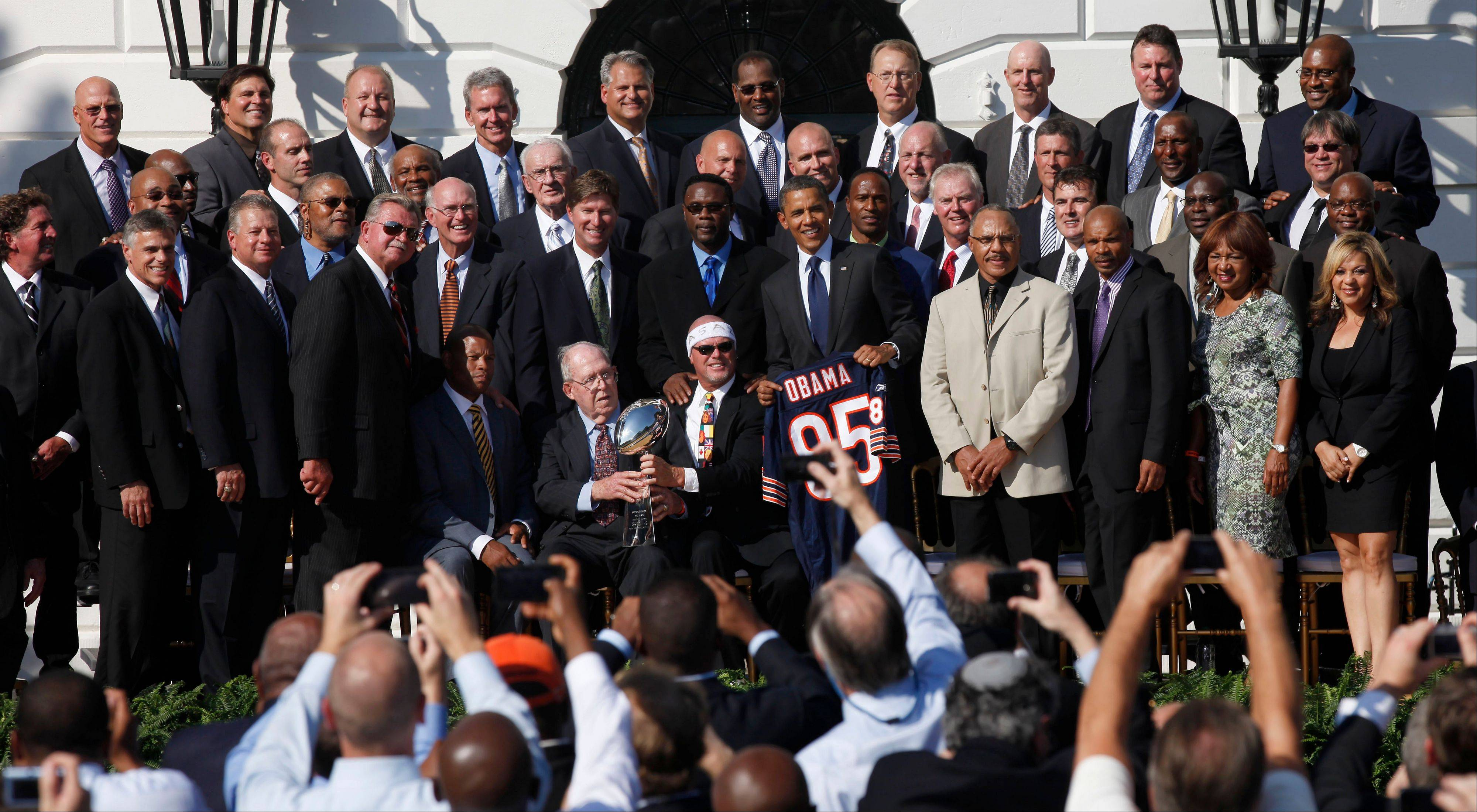 ASSOCIATED PRESSPresident Barack Obama, center, holds up a team jersey as he stands with the 1985 Super Bowl XX Champions Chicago Bears football team during a ceremony on the South Lawn of the White House.