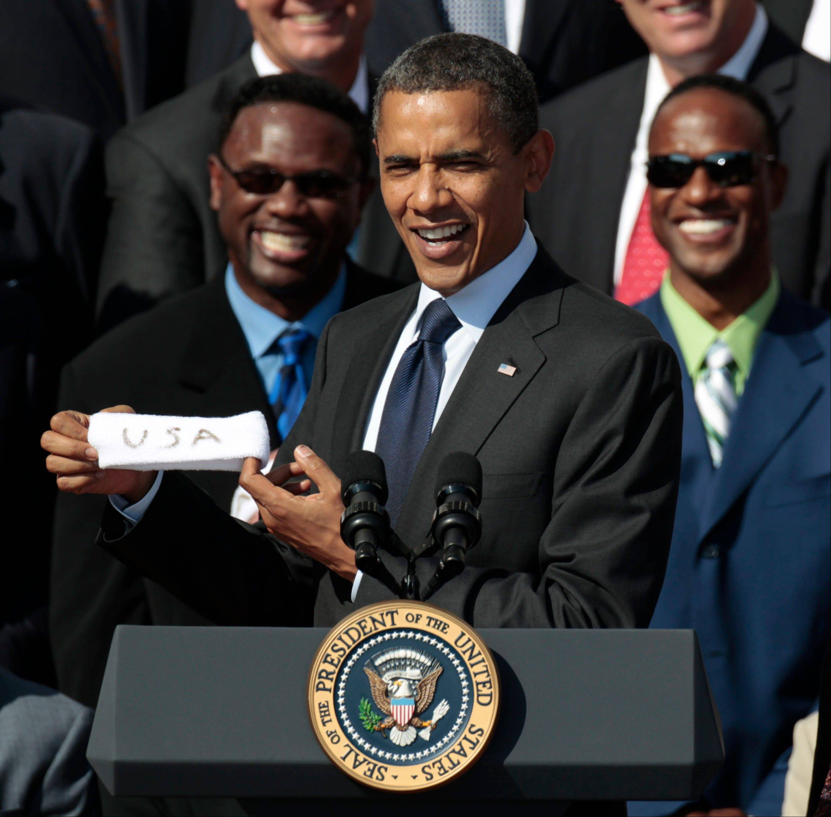 President Barack Obama holds up a headband given to him by former quarterback Jim McMahon, as he honors the 1985 Super Bowl XX Champions Chicago Bears football team during a ceremony on the South Lawn of the White House in Washington, Friday, Oct. 7, 2011.