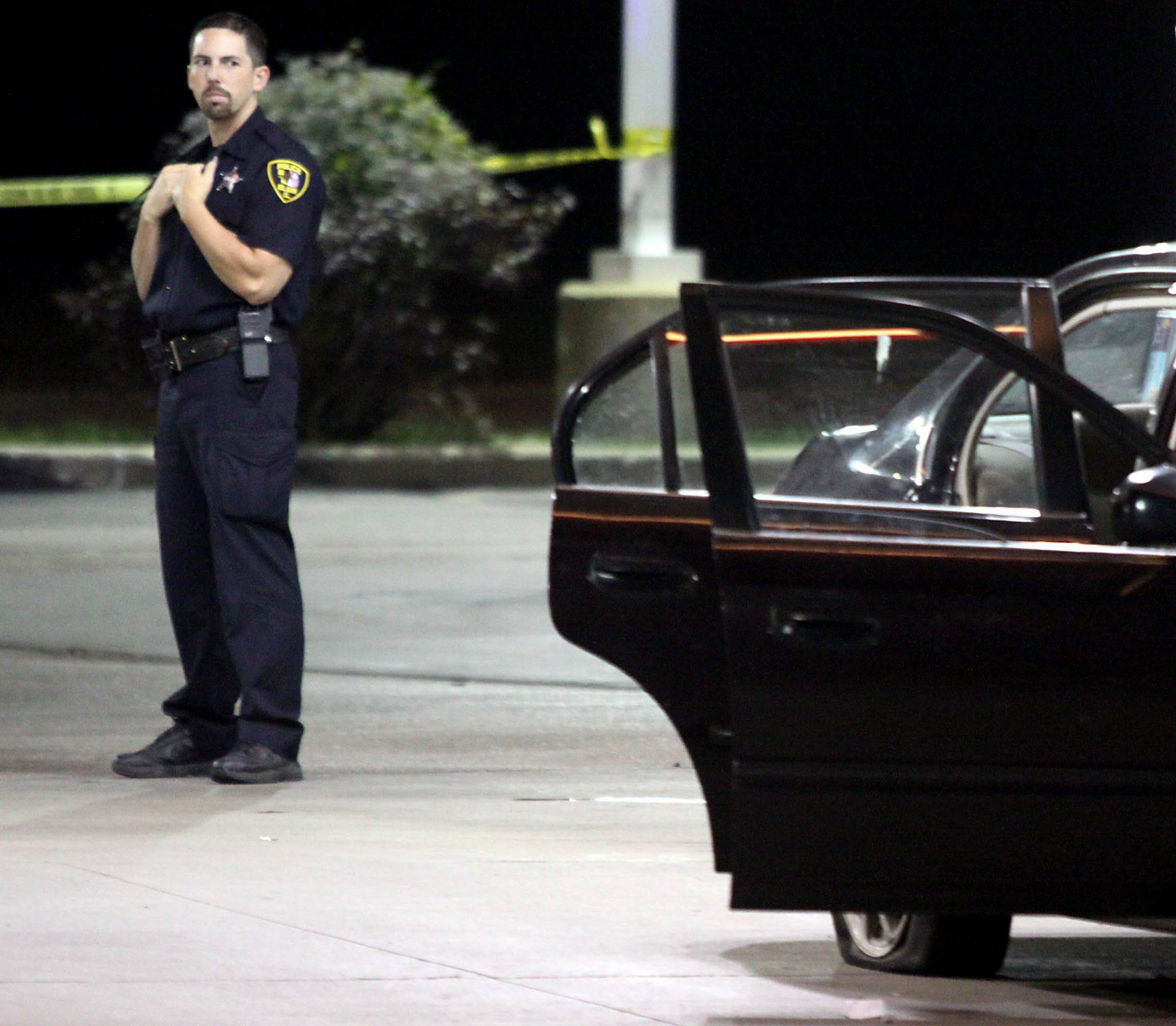 Elgin police investigate after a child with a gunshot wound was transported from a gas station along Dundee Avenue on Friday night. Here, an Elgin police officer surveys the scene at the gas station. The boy later died.
