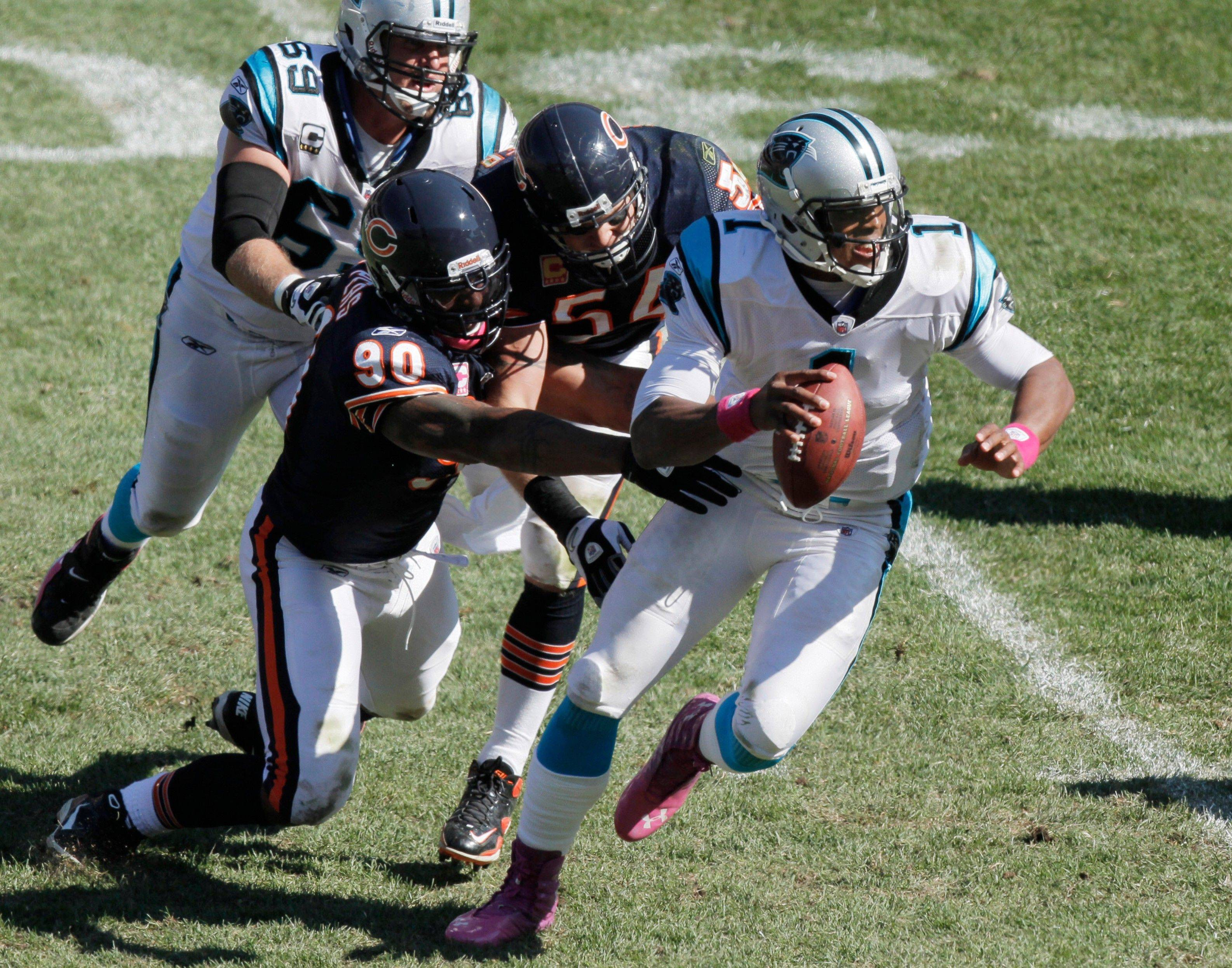 Carolina Panthers quarterback Cam Newton (1) is chased by Chicago Bears defensive end Julius Peppers (90) and linebacker Brian Urlacher (54) in the second half of an NFL football game in Chicago, Sunday, Oct. 2, 2011.