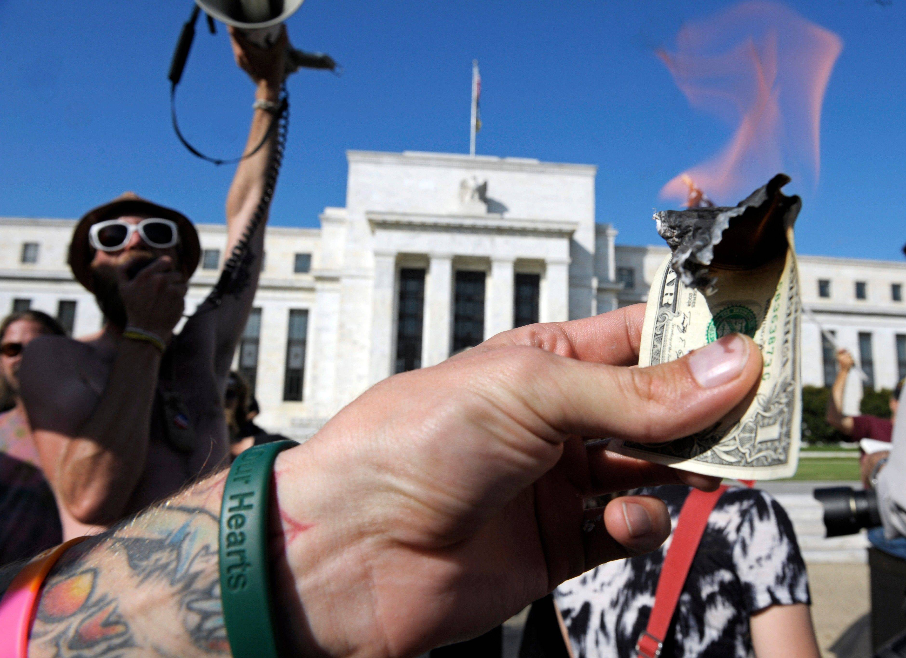Protesters who are calling for an end to the Federal Reserve and are part of the Occupy DC movement burn a dollar bill Sunday in front of the Federal Reserve in Washington.