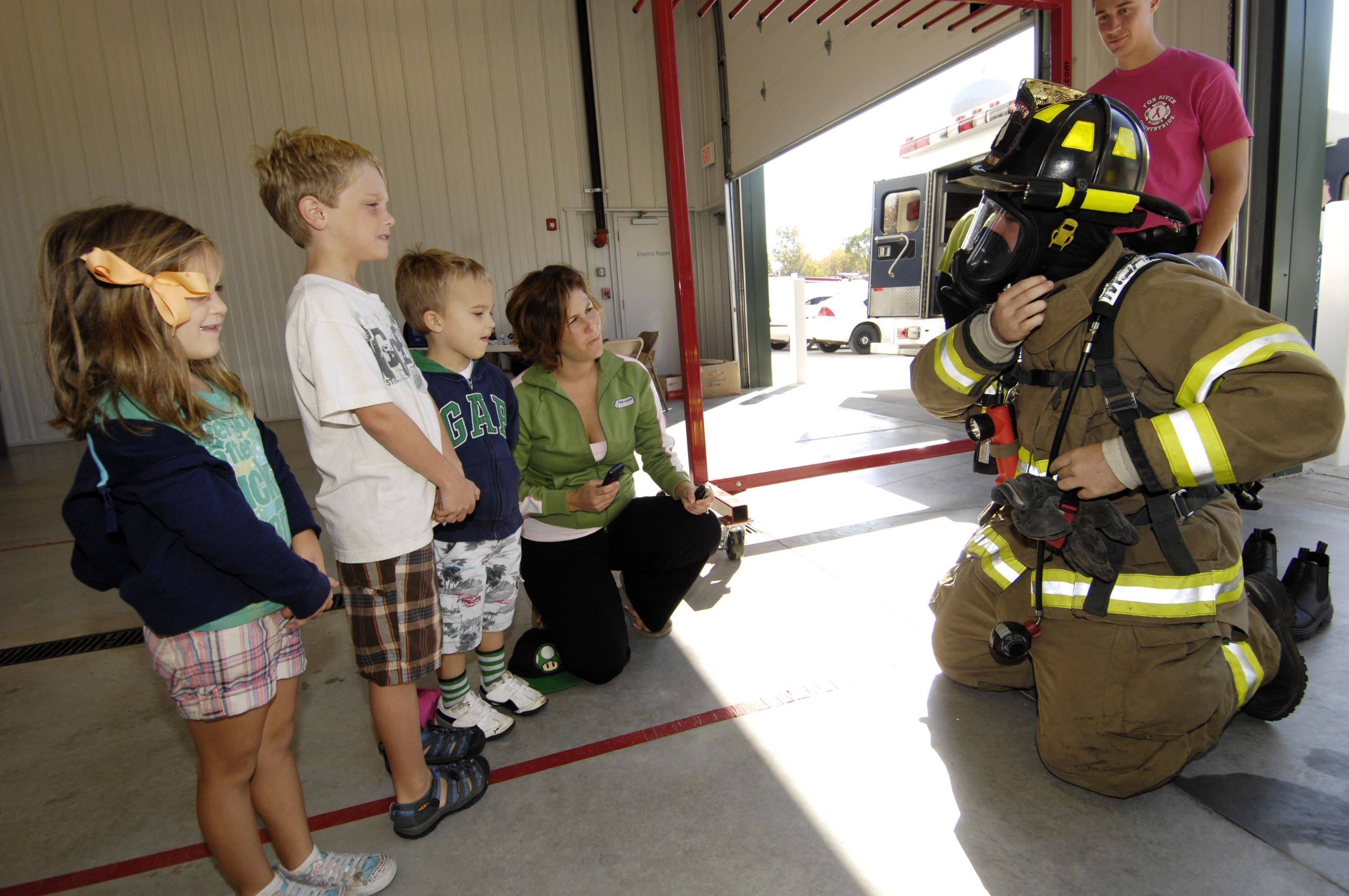 Lilly Webbe, 5, Ryan Freeding, 3, Brett Webbe, 8 and Crissy Webbe watch as firefighter Scott Lyng puts on his gear during the Fox River & Countryside Fire/Rescue District open house on Sunday. The event took place in conjunction with the Remembrance Rescue Project that helps to educate, honor and remember firefighters lost in the 9/11 attacks.