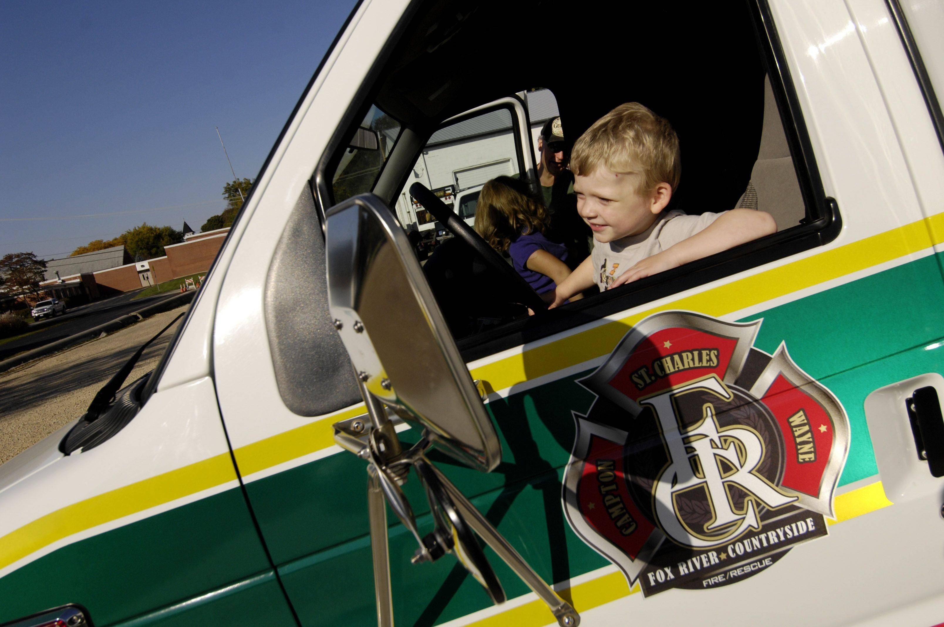 Niklas Thryselius, 3 of St. Charles Township, pretends to drive an ambulance during the Fox River & Countryside Fire/Rescue District open house on Sunday.