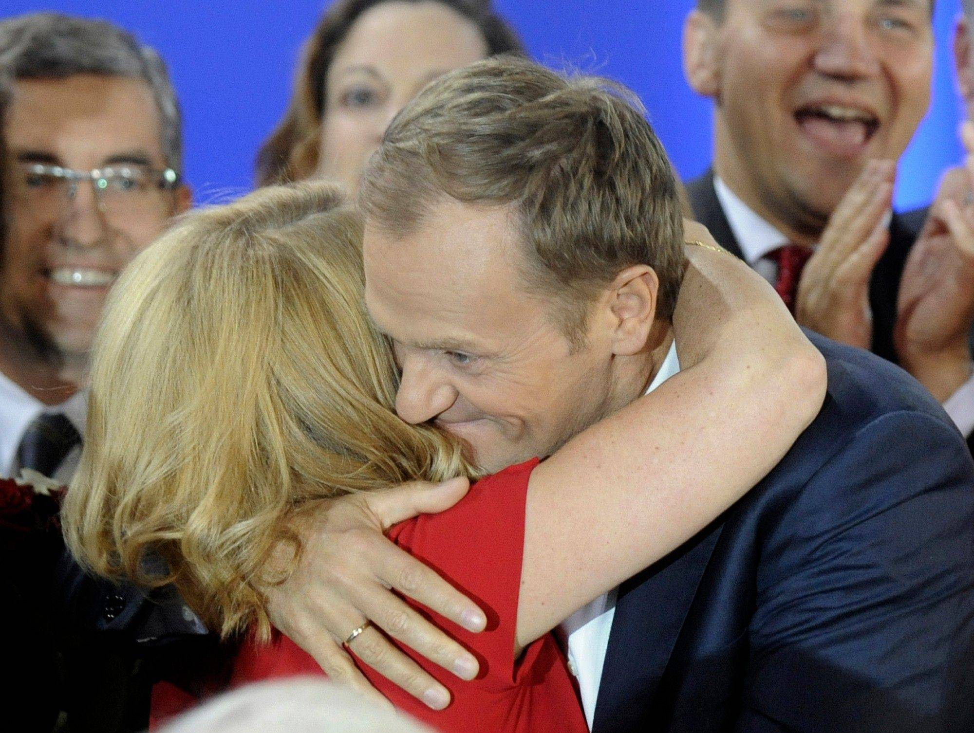 Prime Minister Donald Tusk hugs his wife, Malgorzata, as the first exit poll is published Sunday during the election party of Tusk's Civic Platform, a centrist and pro-EU party, in Warsaw.
