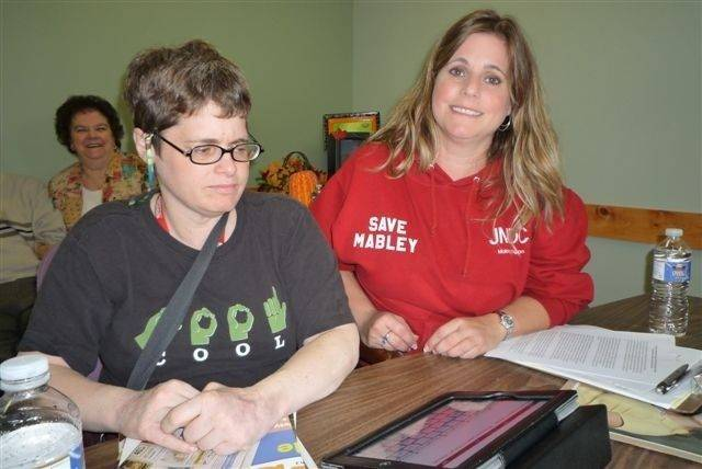 "Wearing her ""Save Mabley"" sweatshirt, social worker Angela Black Childers, right, of Hampshire hopes to save the Jack Mabley Developmental Center in Dixon, where her sister, Dawn, has made a home."