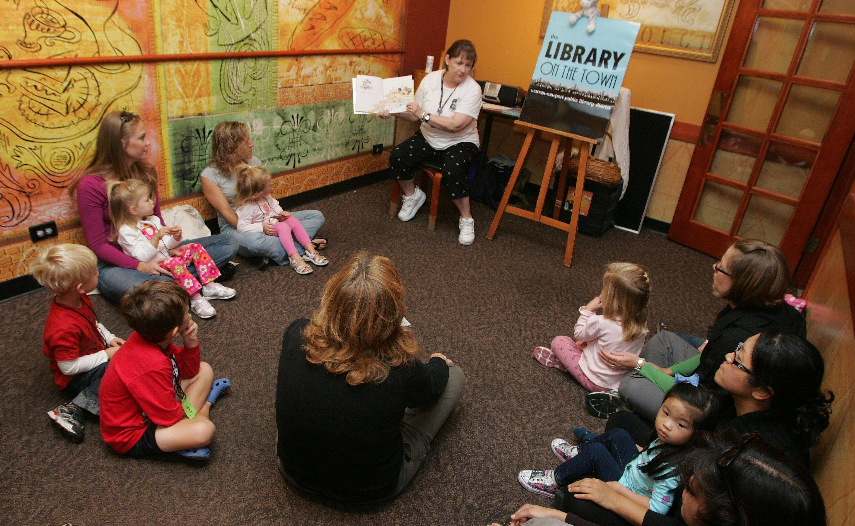 "Children's program specialist Patty Sawin reads ""If You Give the Cat a Cupcake"" during story time for prekindergarten children hosted by Warren-Newport Public Library at a Panera Bread in Gurnee last month. It was part of the Library On The Town program necessitated by closure of the building since Sept. 12 to accommodate final construction work."