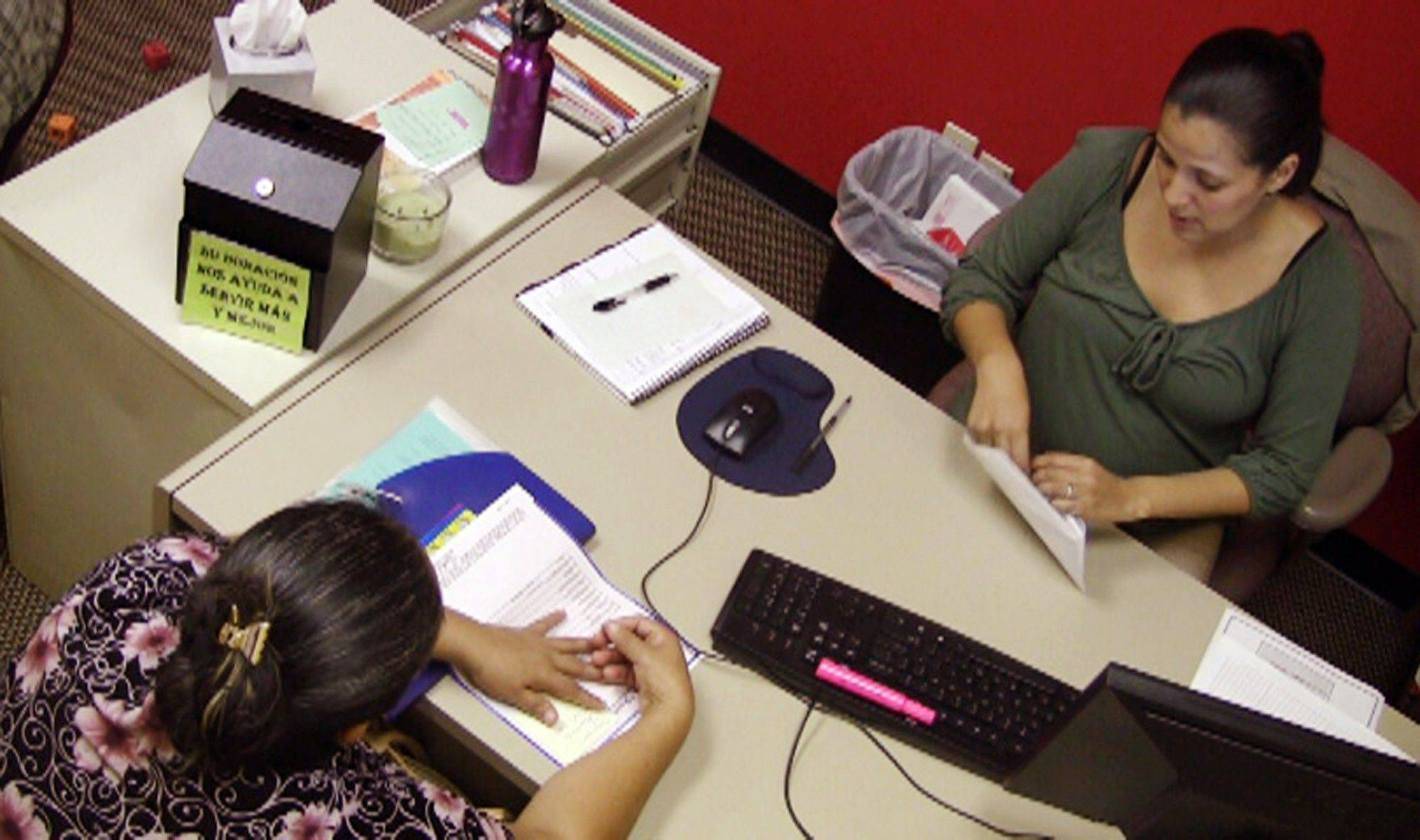 Jazmin Rivera, right, a case manager with the Hispanic Interest Coalition of Alabama, works with an unidentified immigrant in her office in Birmingham, Ala. Parents living in the country illegally are scared of deportation under Alabama's new immigration law, and Rivera has helped many with paperwork to provide care for their children in case the parents are arrested.