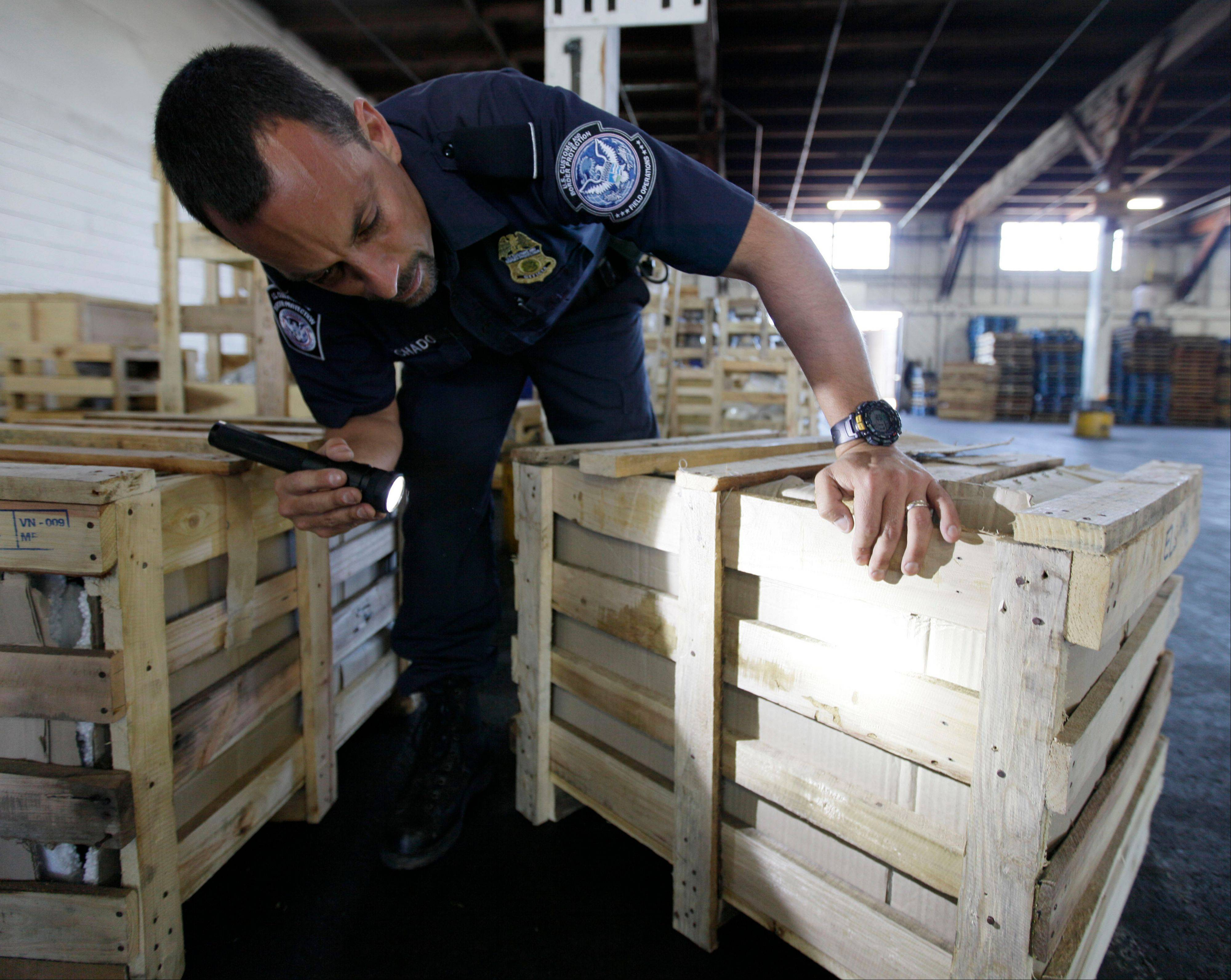 Agriculture specialist John Machado, with U.S. Customs and Border Protection, spots a wooden crate that a pest had bore into at bottom right, during an inspection in Oakland, Calif., Tuesday Aug. 23, 2011. Dozens of foreign insects and plant diseases slipped undetected into the United States in the years after 9/11, when authorities were so focused on preventing another attack that they overlooked a pest explosion that threatened the quality of the nation�s food supply.