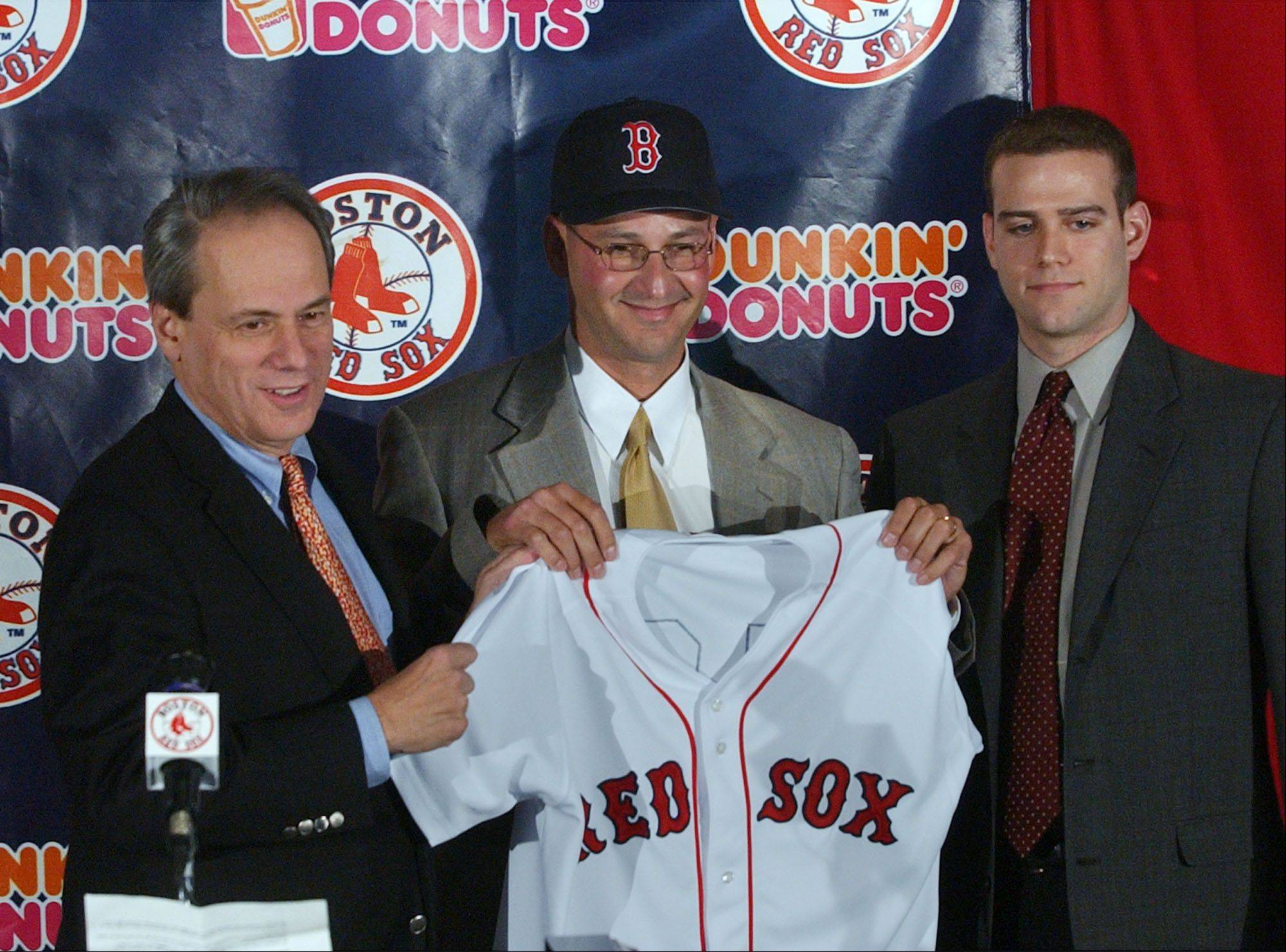Former Philadelphia Phillies manager Terry Francona, center, shows his new Boston Red Sox uniform during a news conference at Fenway Park in Boston, Thursday, Dec. 4, 2003 with Red Sox President Larry Lucchino, left, and General Manager Theo Epstein, right. Boston Red Sox named Francona their 44th manager.