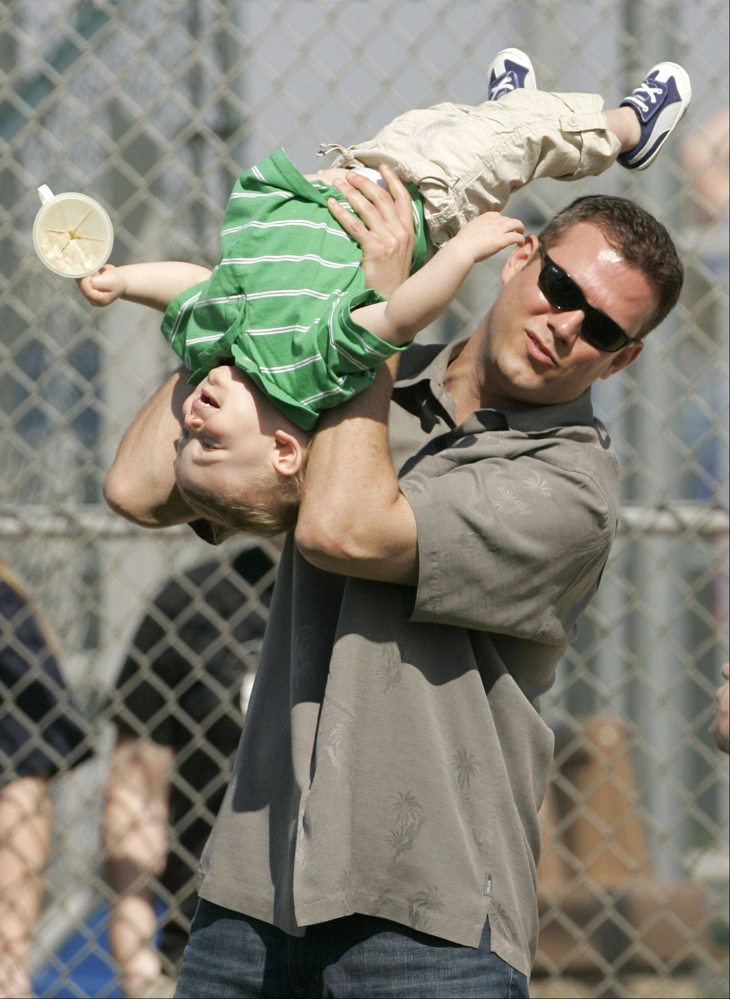 Boston Red Sox general manager Theo Epstein plays with his son, Jack, during a baseball spring training workout, in Fort Myers, Fla., Wednesday, Feb. 18, 2009.
