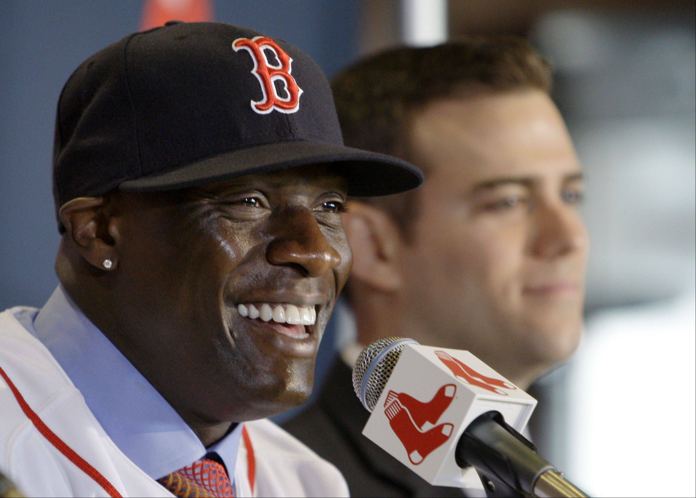 Newly-acquired Boston Red Sox outfielder Mike Cameron, left, smiles as he sits next to Red Sox general manager Theo Epstein during a baseball news conference at Fenway Park in Boston, Wednesday, Dec. 16, 2009. Cameron signed a two-year contract with the Red Sox worth a reported $7 million to $8 million a season.
