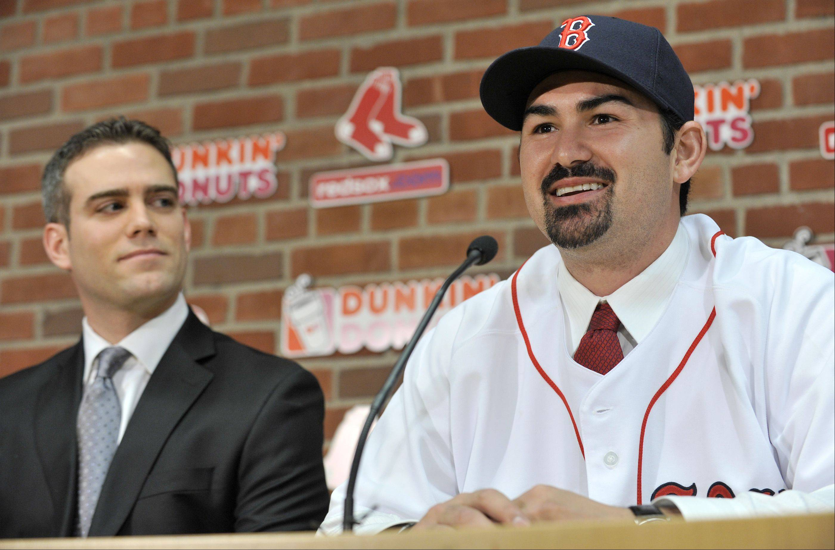 New Boston Red Sox first baseman Adrian Gonzalez, right, speaks to reporters as Red Sox General Manager Theo Epstein, left, looks on during a news conference at Fenway Park in Boston, Monday, Dec. 6, 2010. The Red Sox finally landed the All-Star first baseman, acquiring him from the San Diego Padres in exchange for three prospects and a player to be named later.
