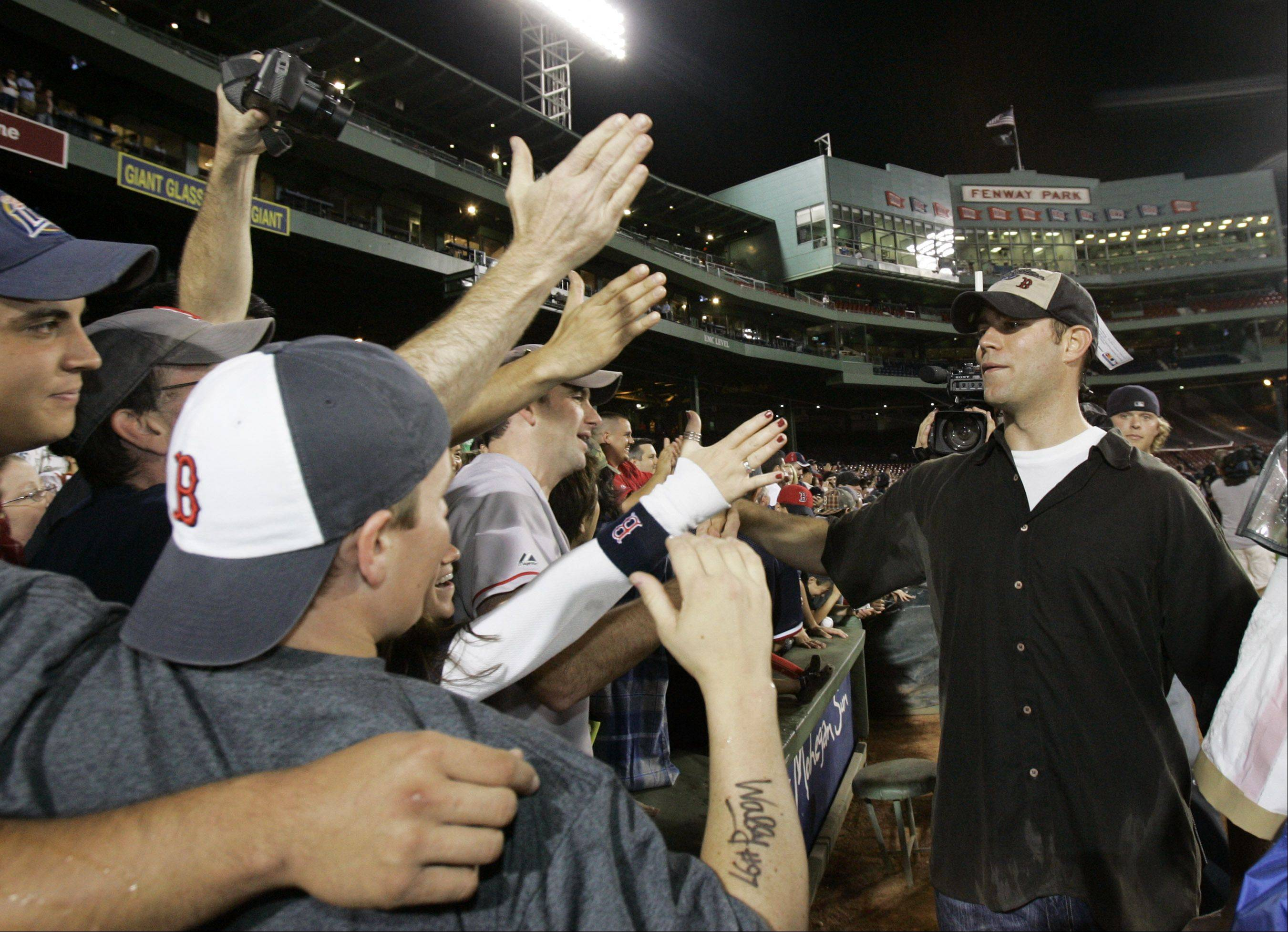 Boston Red Sox general manager Theo Epstein, right, slaps hands with fans at Fenway Park in Boston, Friday, Sept. 28, 2007, as they celebrate clinching the AL East.
