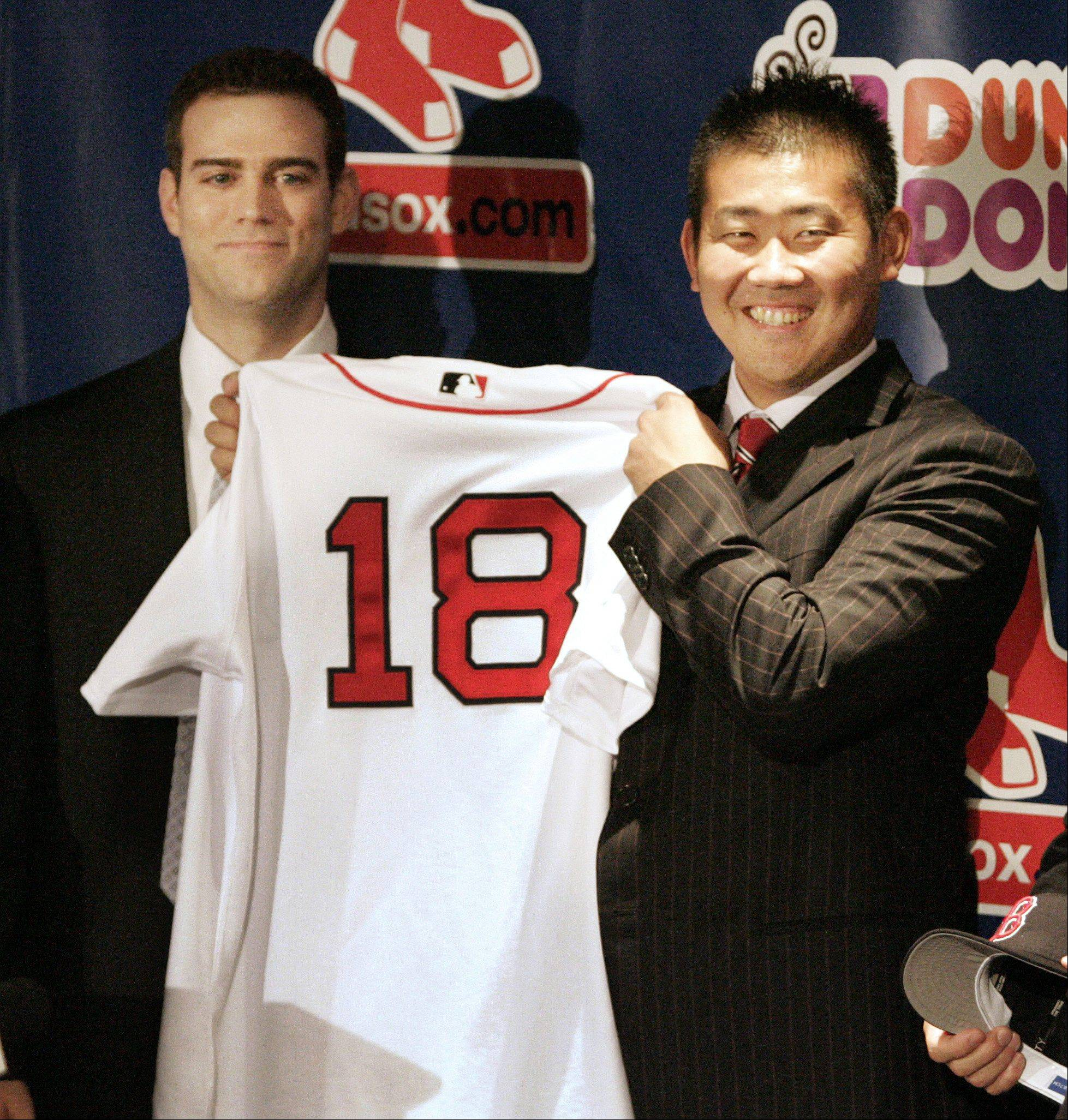 Newly signed Boston Red Sox Japanese pitcher Daisuke Matsuzaka, right, displays his new Red Sox jersey as team manager Theo Epstein, left, looks on during a news conference held to announce the signing, in Boston, Thursday, Dec. 14, 2006.