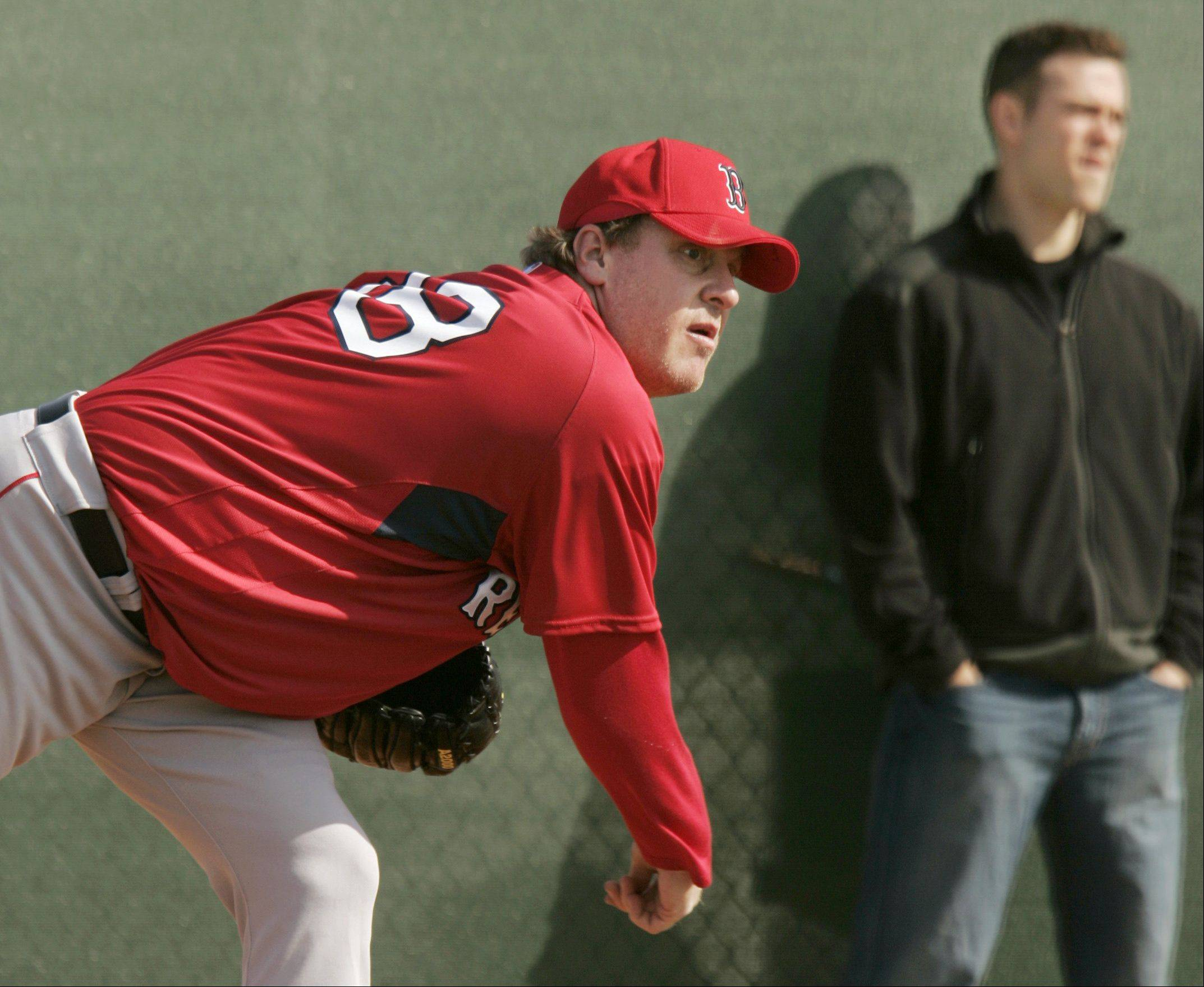 Boston Red Sox pitcher Curt Schilling, left, delivers a throw as Red Sox general manager Theo Epstein, right, looks on at baseball spring training at the team's minor league training complex, in Fort Myers, Fla., Sunday, Feb. 18, 2007.