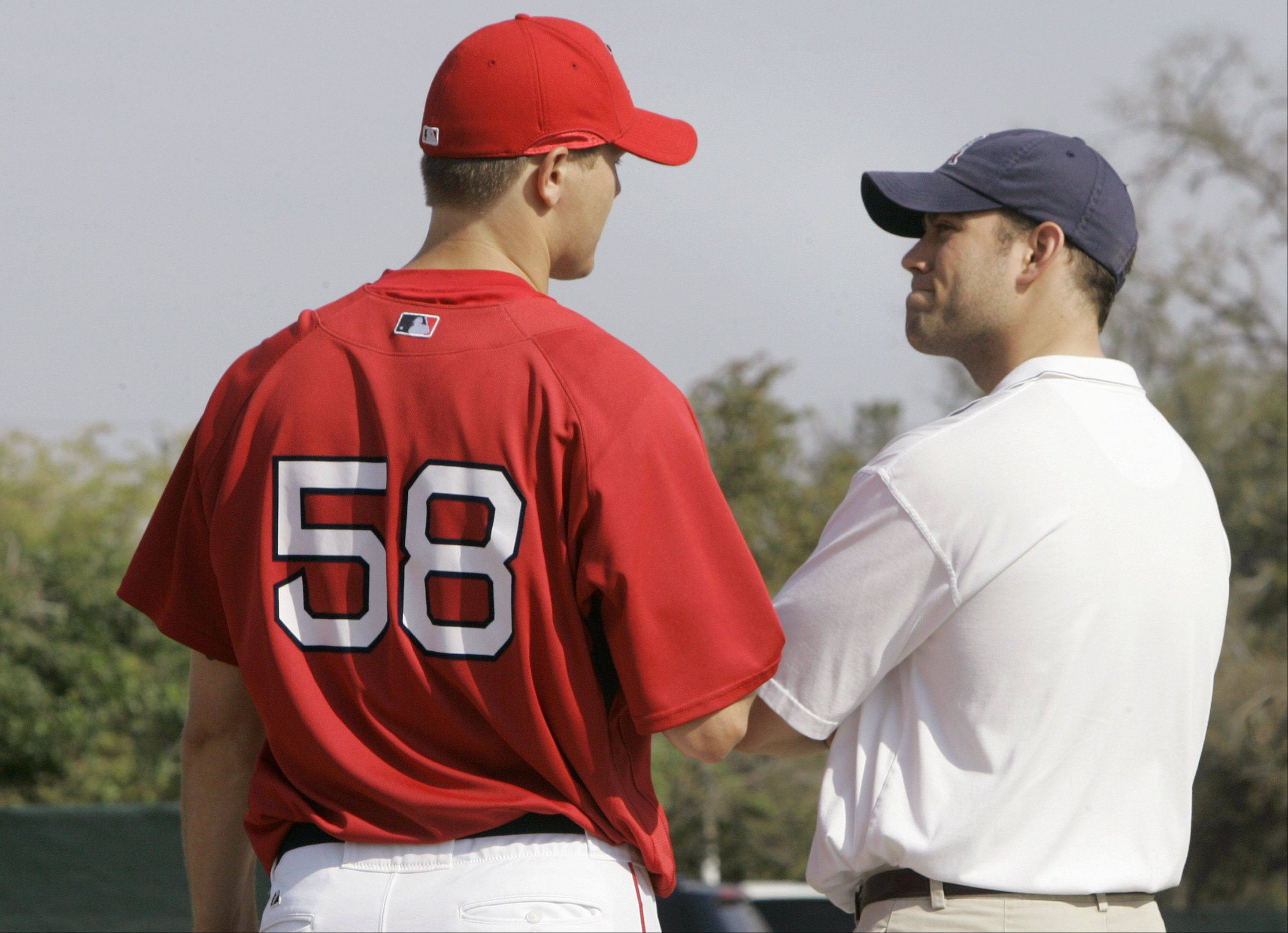 Boston Red Sox pitcher Jonathan Papelbon, left, talks with general manager Theo Epstein during a spring training baseball practice in Fort Myers, Fla., Wednesday March 14, 2007. Papelbon was switched from a closer to a starter this spring, but the Red Sox have moved the 26-year-old right-hander back into the closer role to fill a major void in the bullpen.