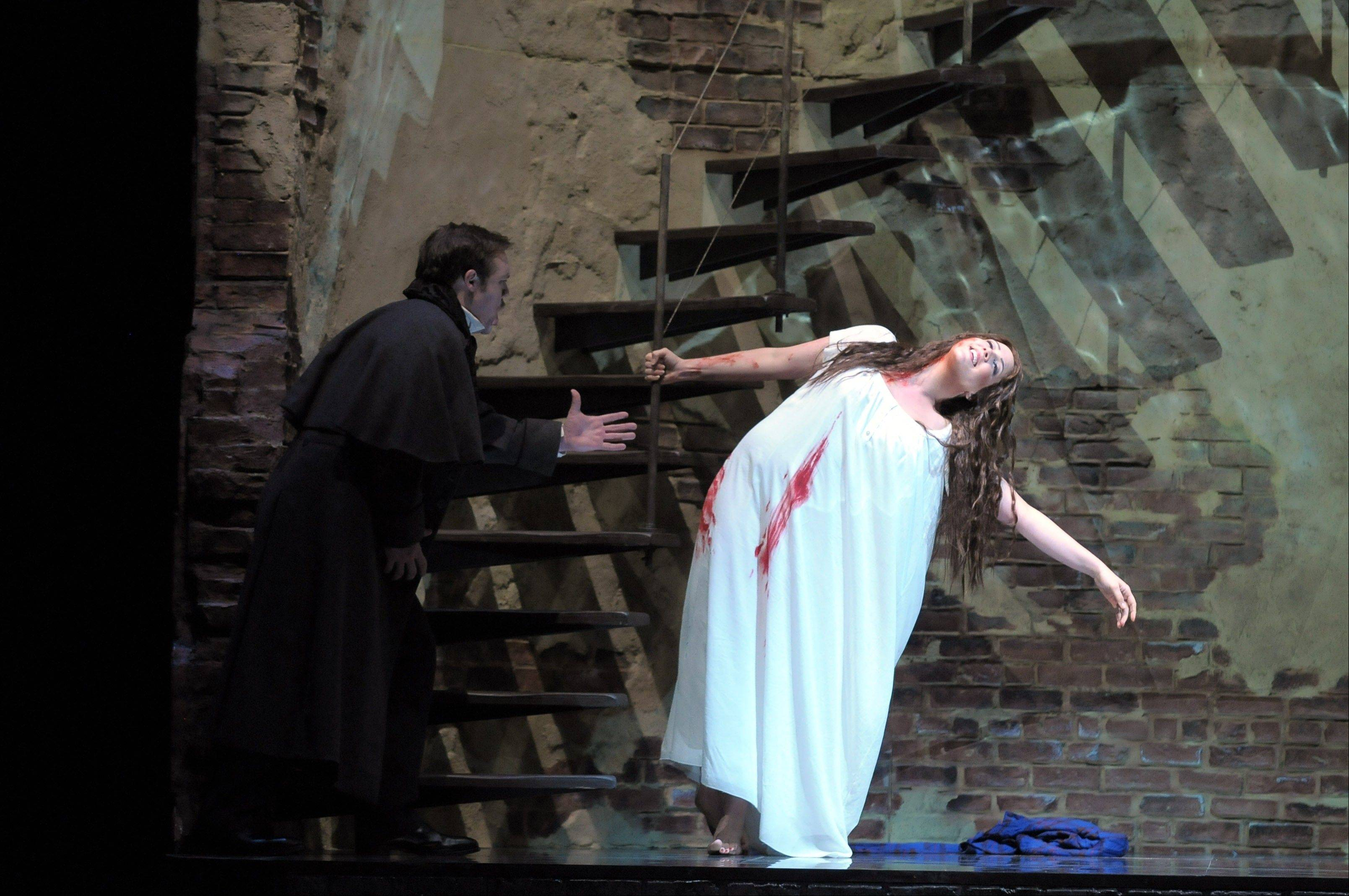 "Lucia (Susanna Phillips) goes murderously mad on her wedding night, much to the dismay of her brother, Enrico (Brian Mulligan, left), in the Lyric Opera of Chicago's new staging of Donizetti's tragedy ""Lucia di Lammermoor,"" directed by soprano Catherine Malfitano."