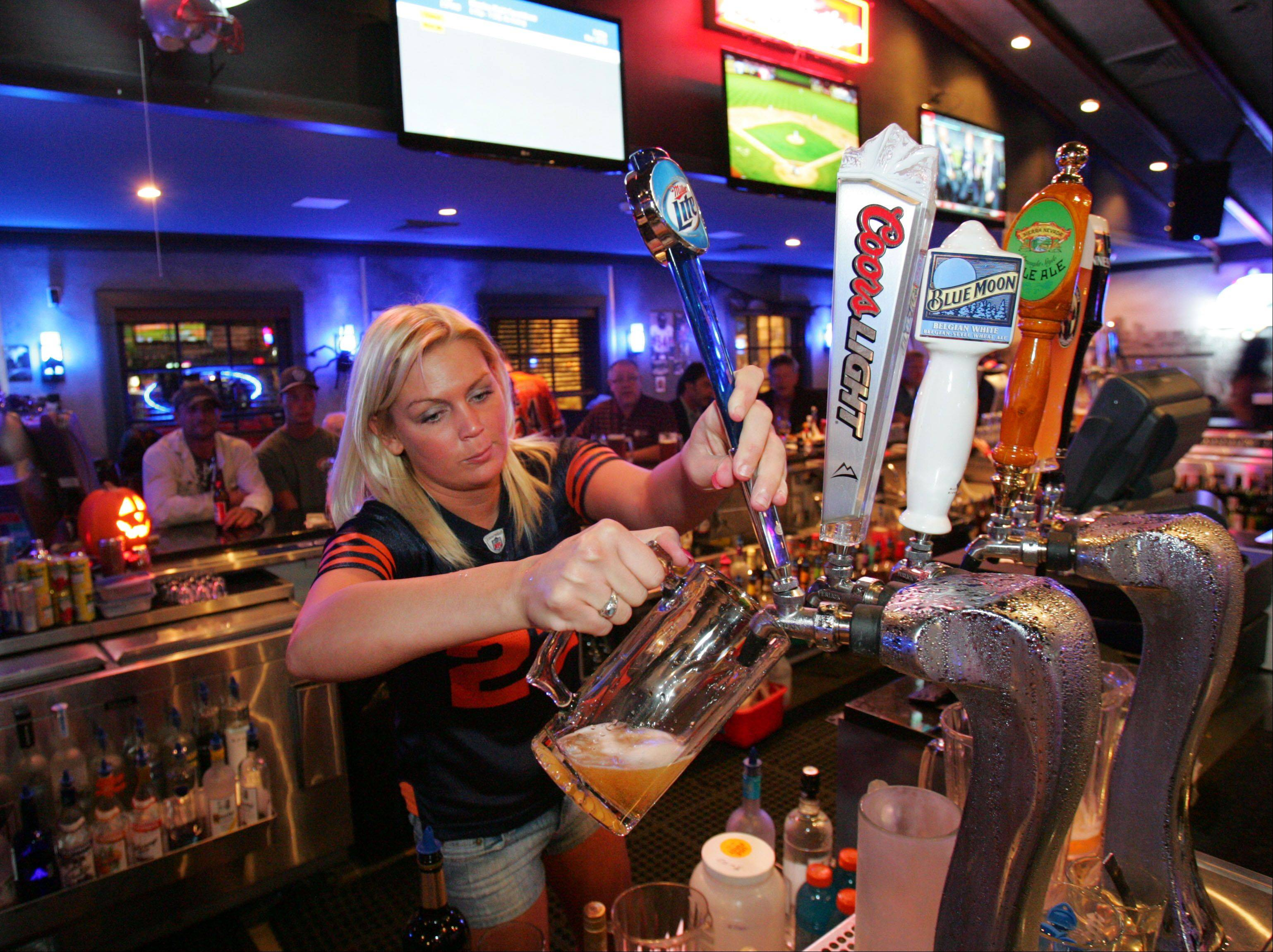 Bartender Jen Kirk pours a beer at Blue 60 sports bar in Mundelein.