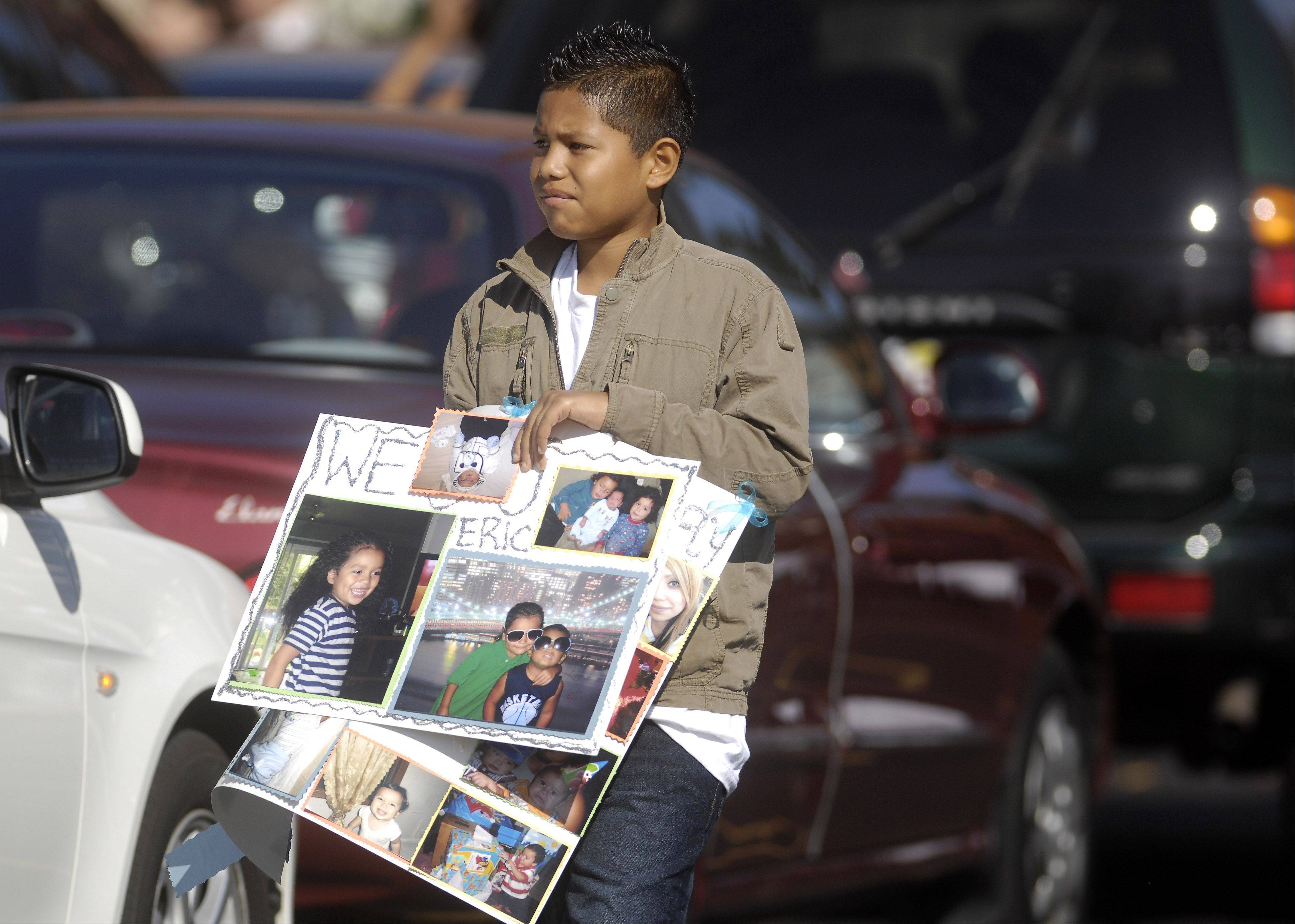 A boy carries a collage of photos Wednesday following the funeral of Eric M. Galarza Jr. at St. Joseph Catholic Church in Elgin