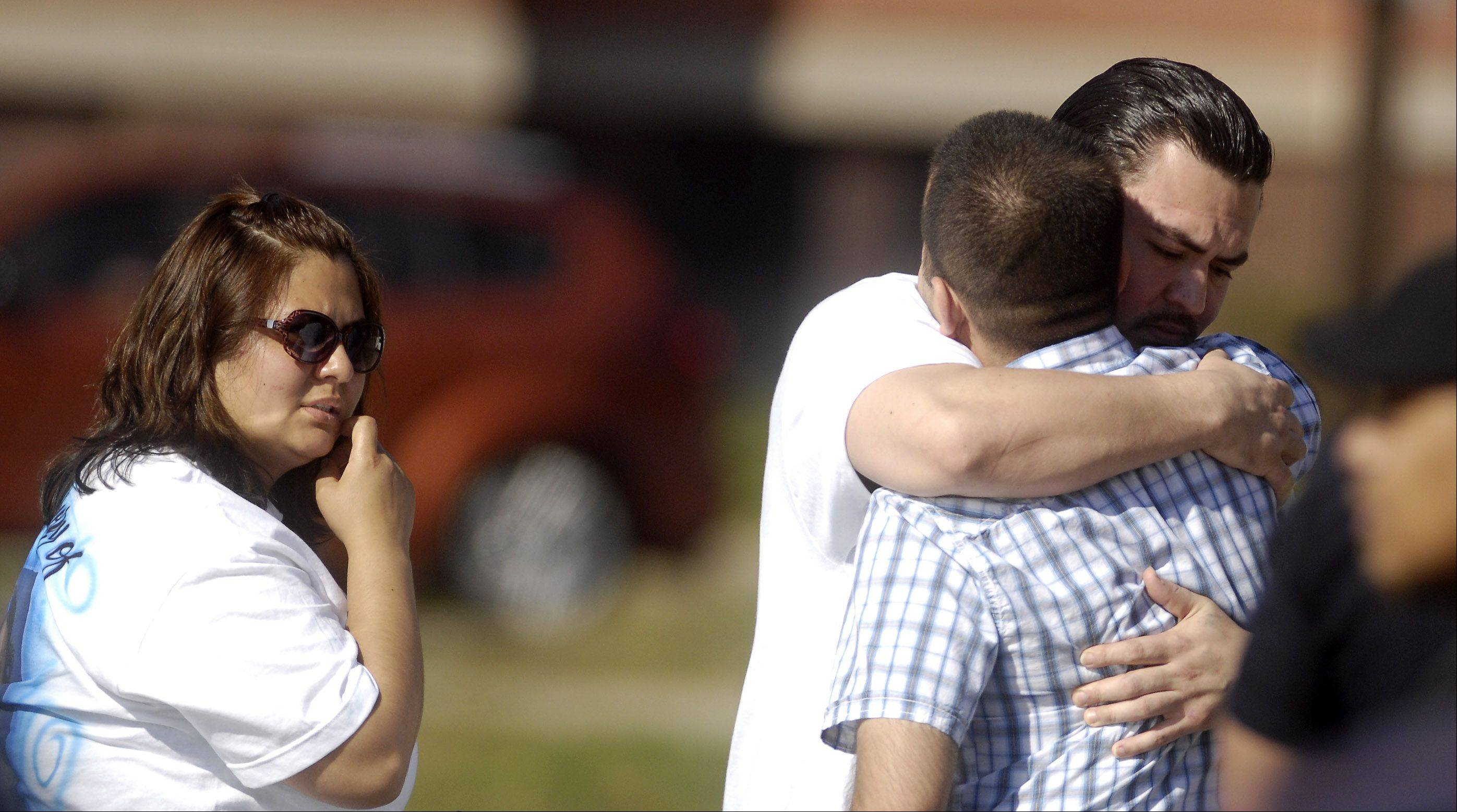 Eric Galarza, right, facing, is hugged by a well-wisher following the funeral Wednesday for his 5-year-old son Eric Jr.